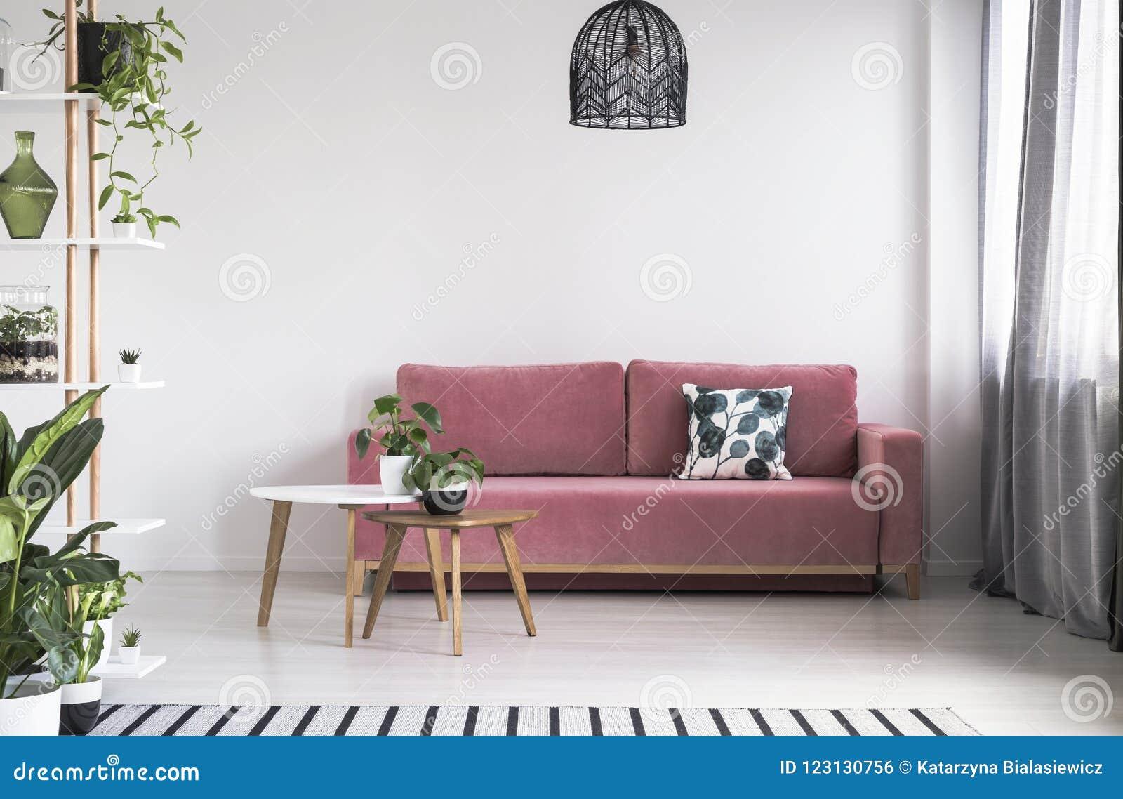 Planta na tabela na frente do sofá vermelho no interior brilhante da sala de visitas com lâmpada Foto real