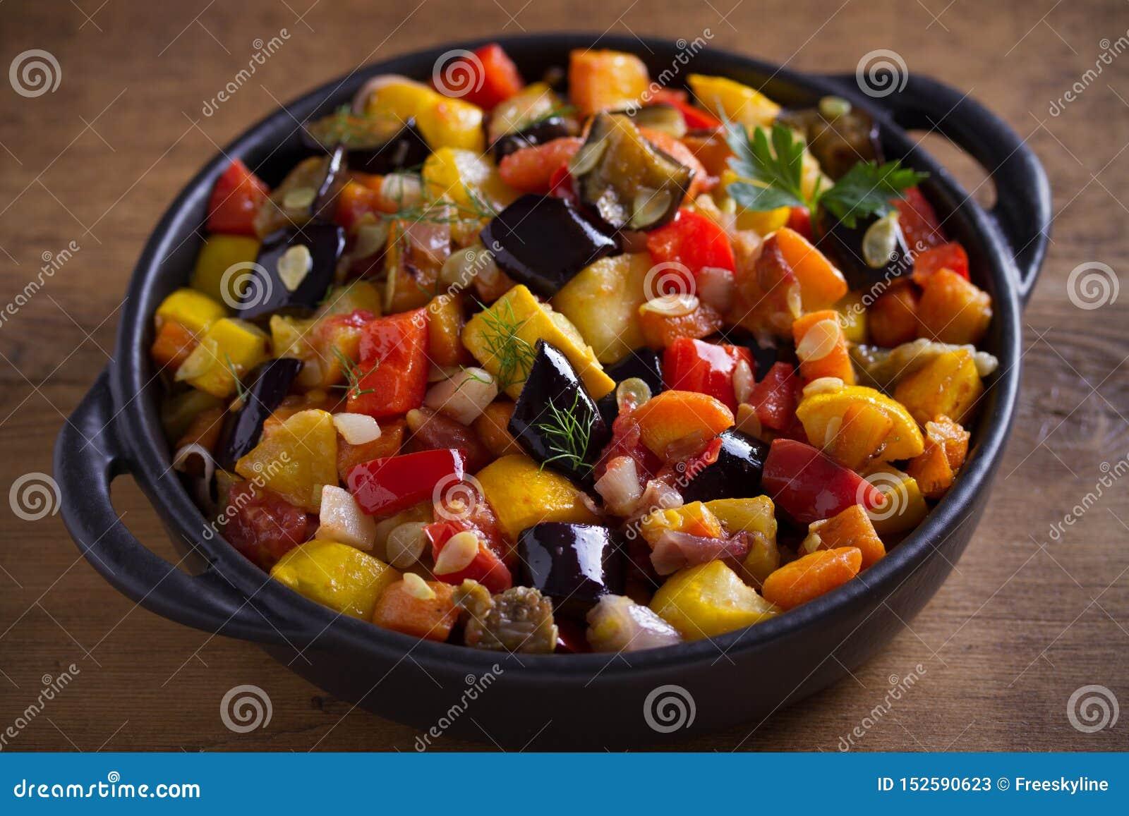 Plantaardige hutspot: aubergines, paprikapeper, tomaten, courgette, wortelen en uien Gestoofde plantaardige salade