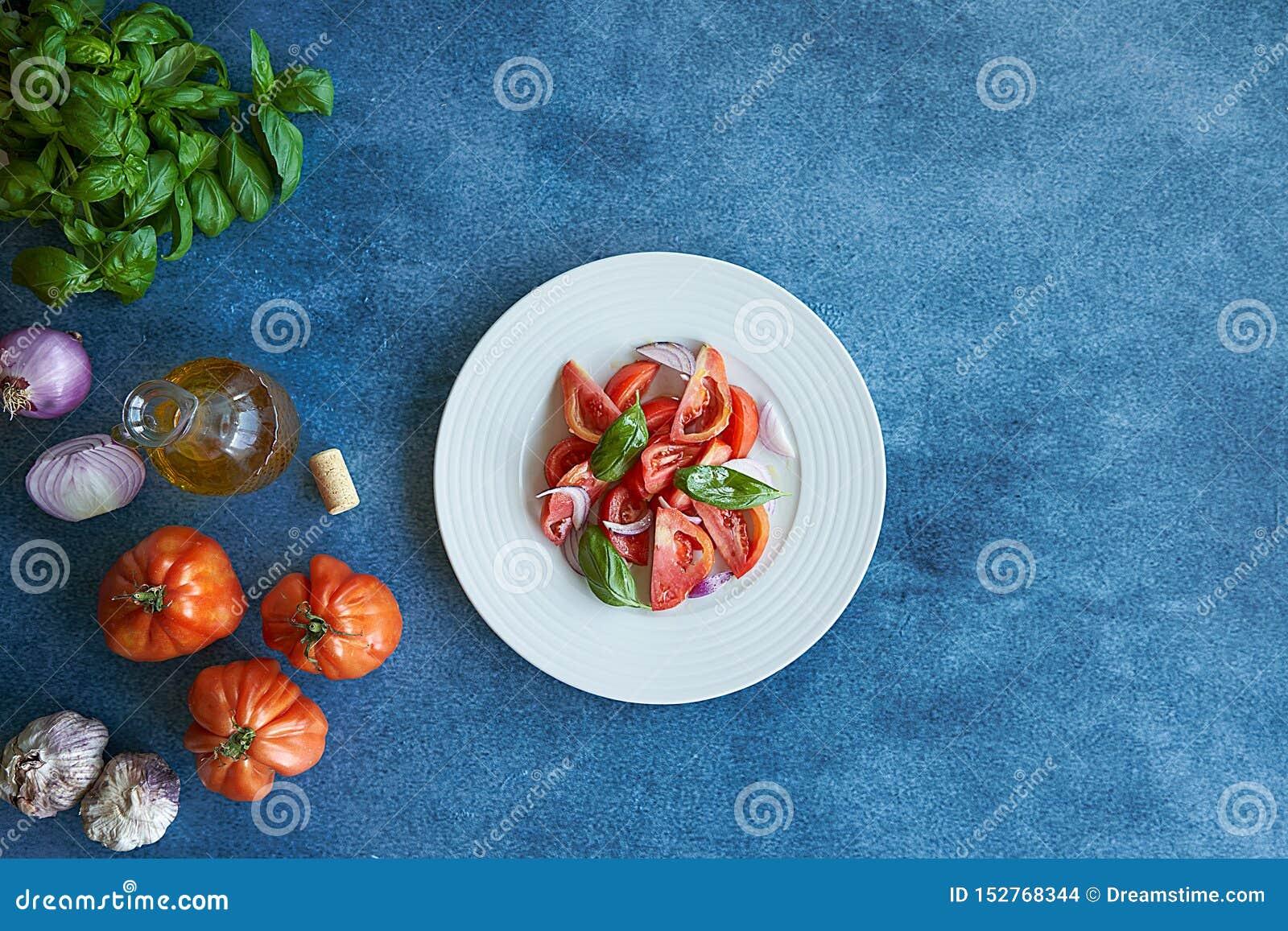 Plantaardige tomatensalade met extra eerste persing, purpere ui, purper knoflook en basilicum Begeleid door een fles van extra ma