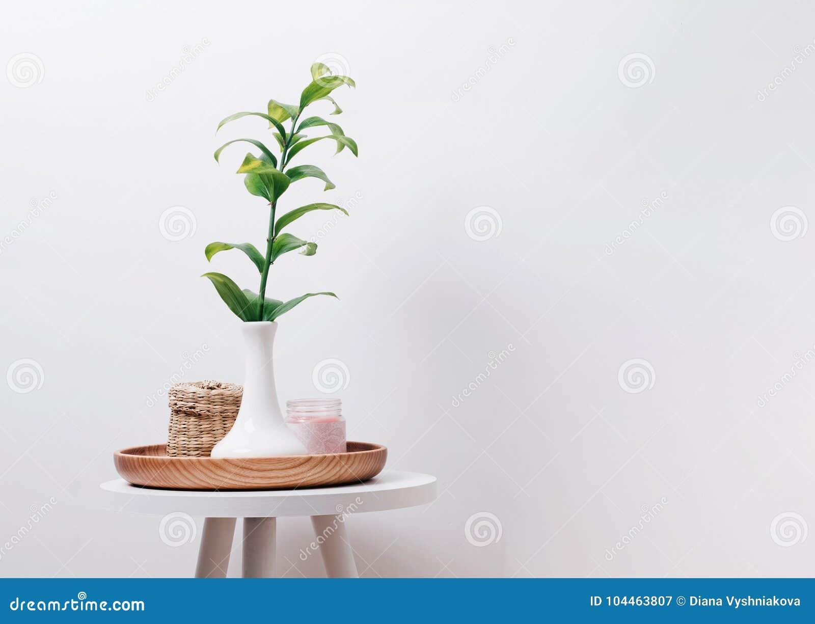 Plante verte dans la boîte de vase, de bougie et de paille sur la petite table