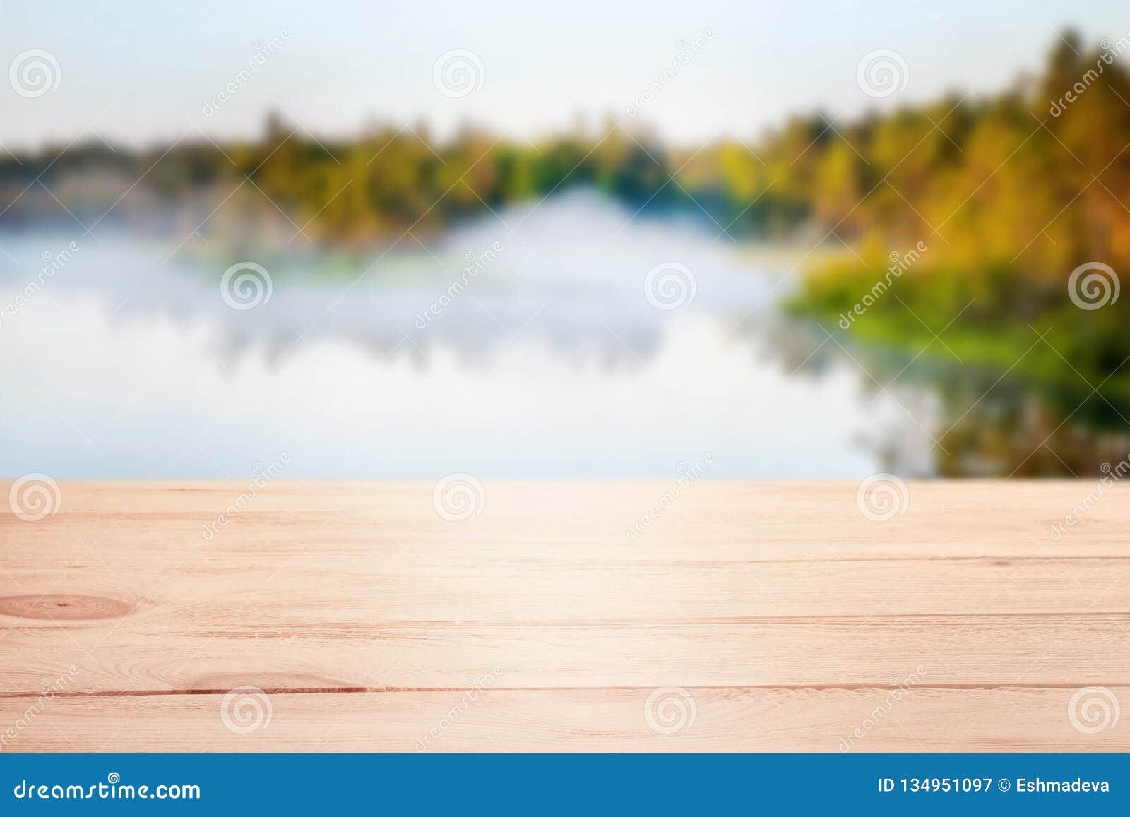 Plantilla de madera de la tabla con el fondo defocused distante del lago del bosque