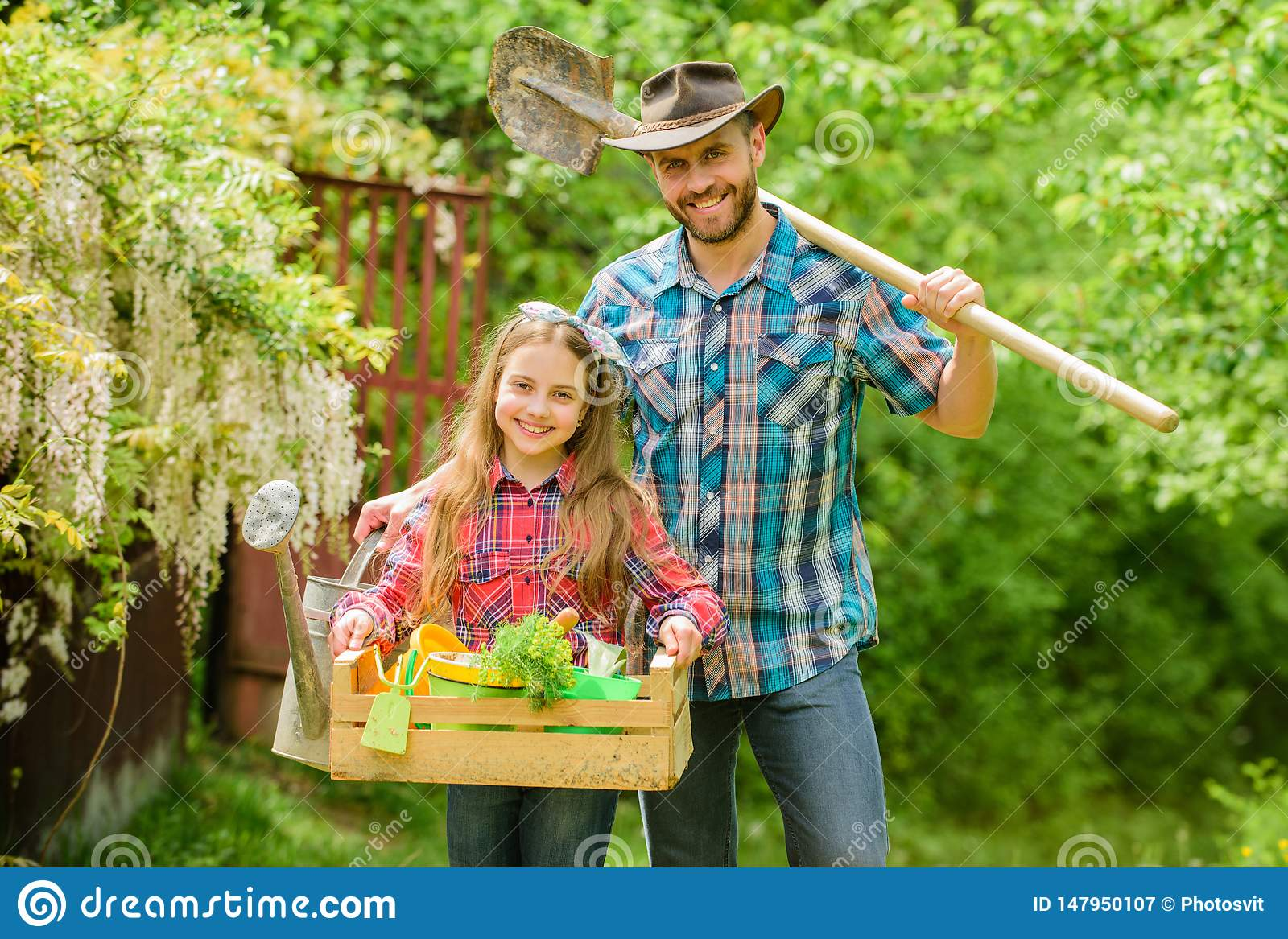 Planting season. Inspect your garden daily to spot insect trouble early. Family dad and daughter little girl planting