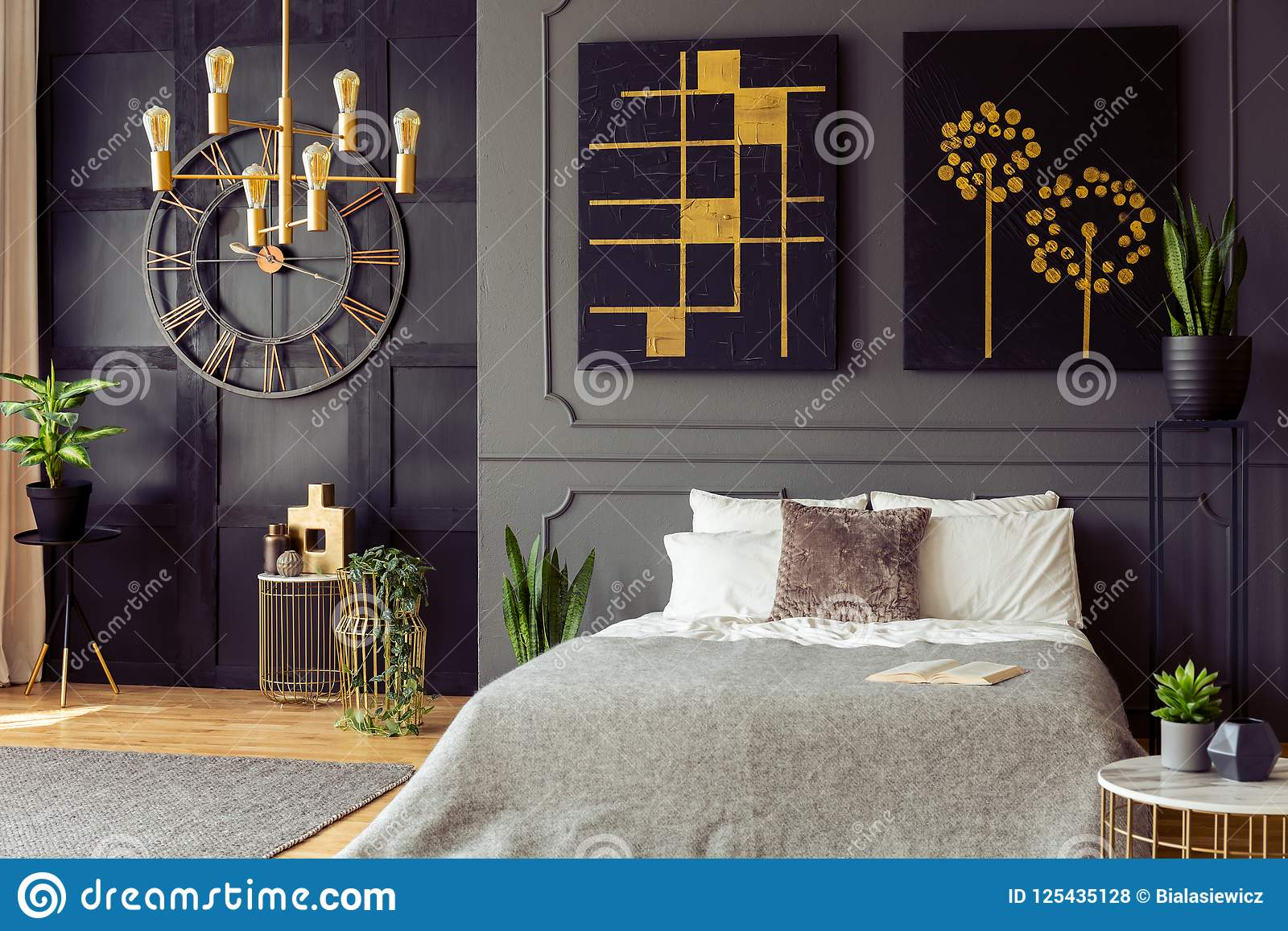 Plants And Black And Gold Posters In Grey Bedroom Interior With Clock And Bed With Pillows Real Photo Stock Photo Image Of Real Room 125435128