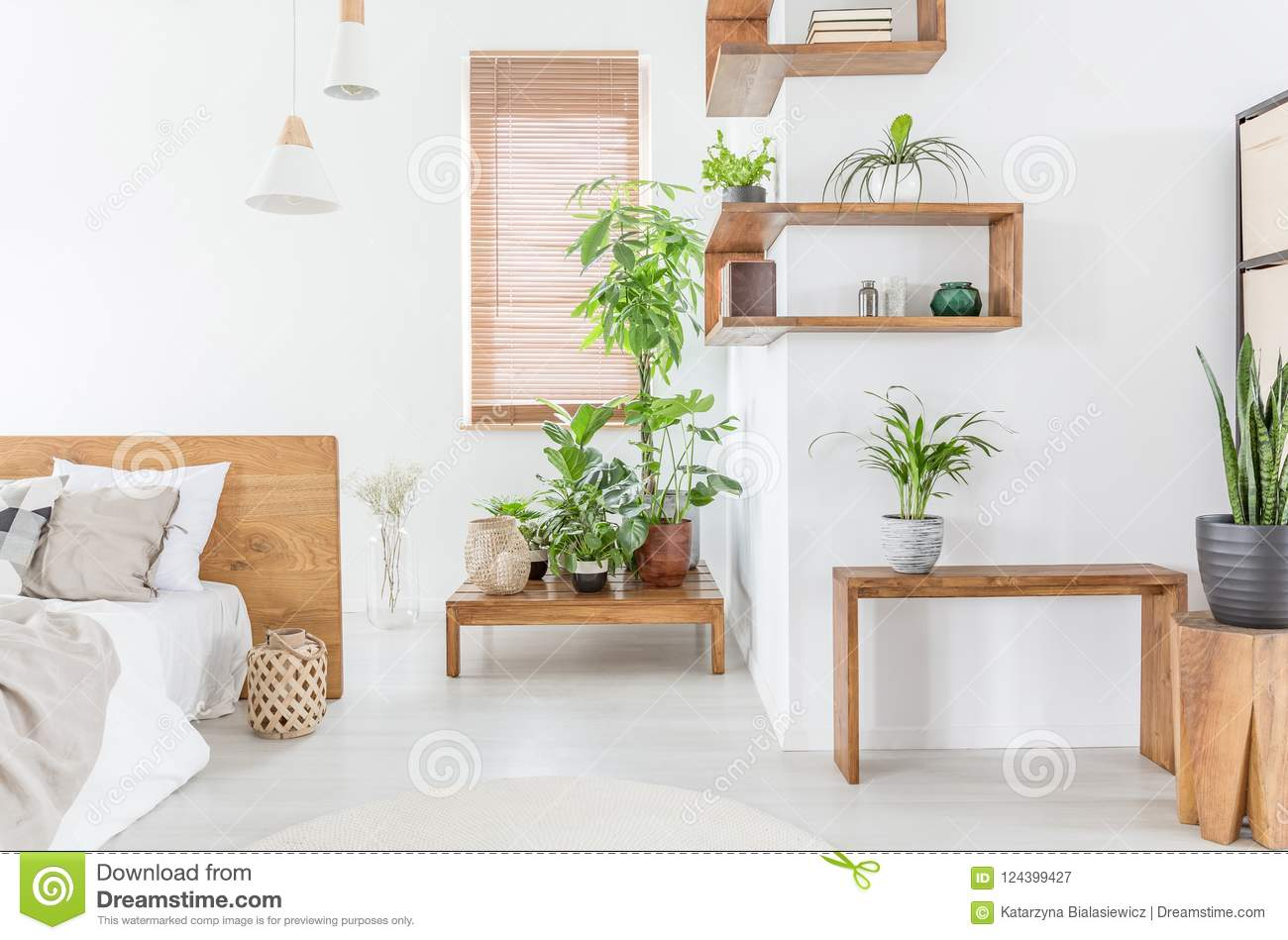 Plants On Wooden Table In White Bedroom Interior With Bed Next To Window  With Blinds.