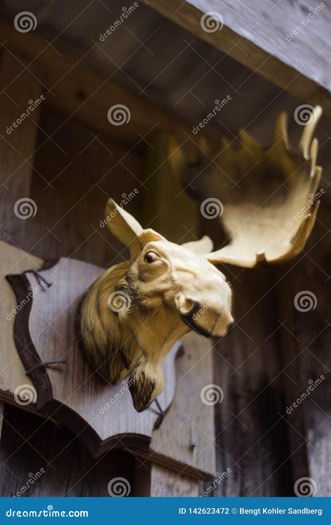 Plast- älghuvud som utanför monteras i en enkel plankavägg Älgen missa ett horn och leenden