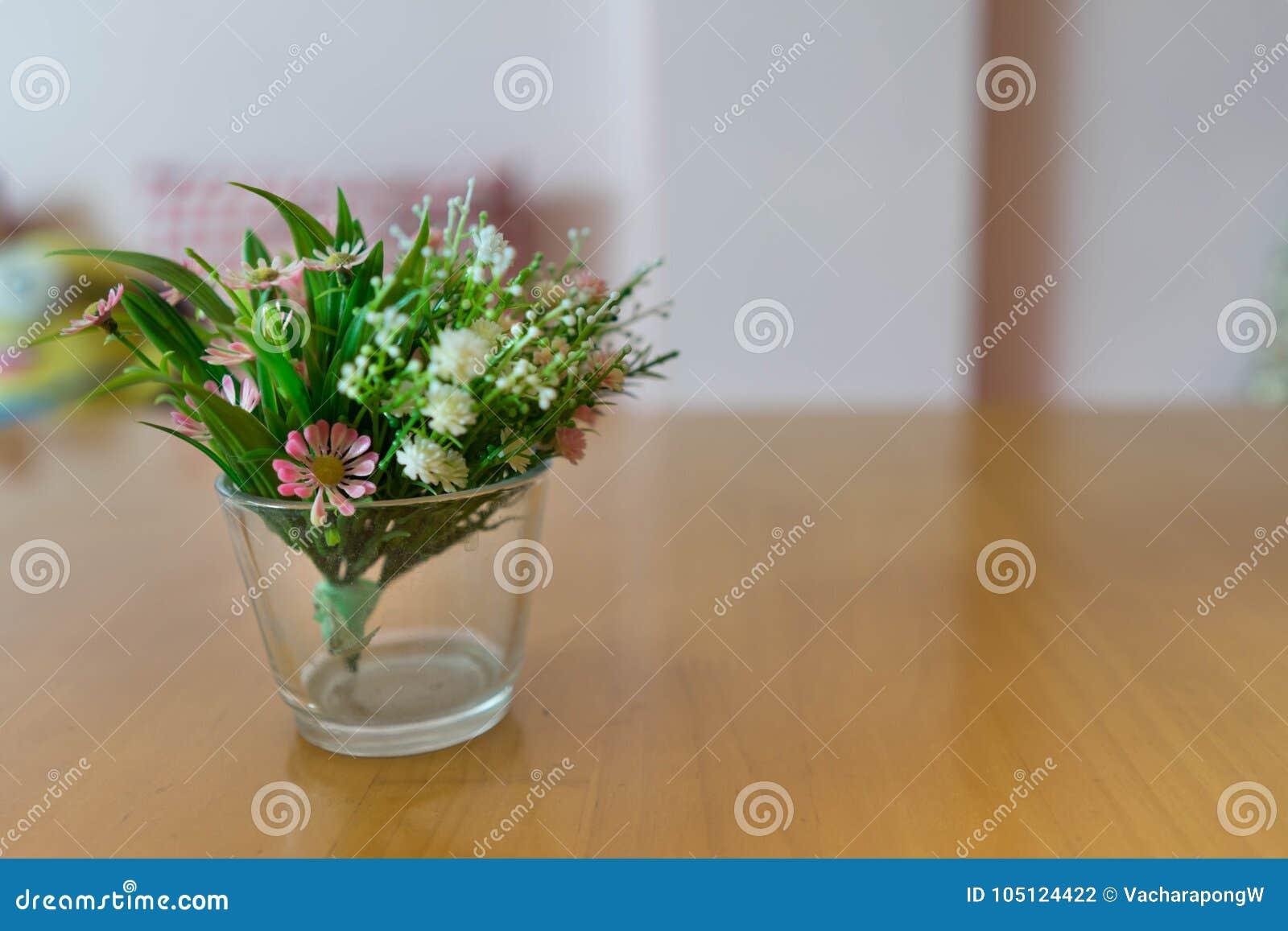 Plast- blommar i vas på träför tabell och rosa väggbackg för suddighet