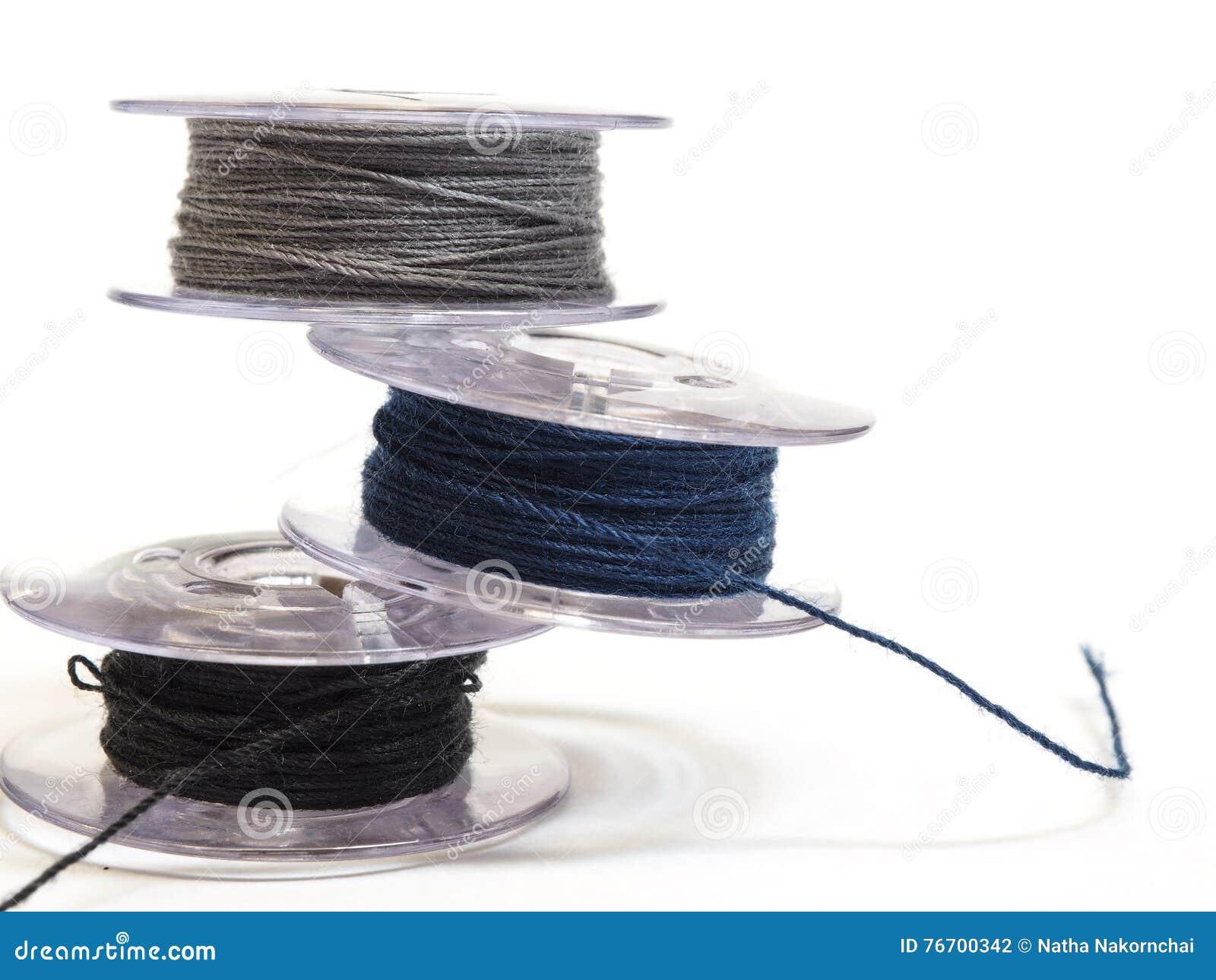 Plast- rulle tre av trådar för symaskin på en vitbac