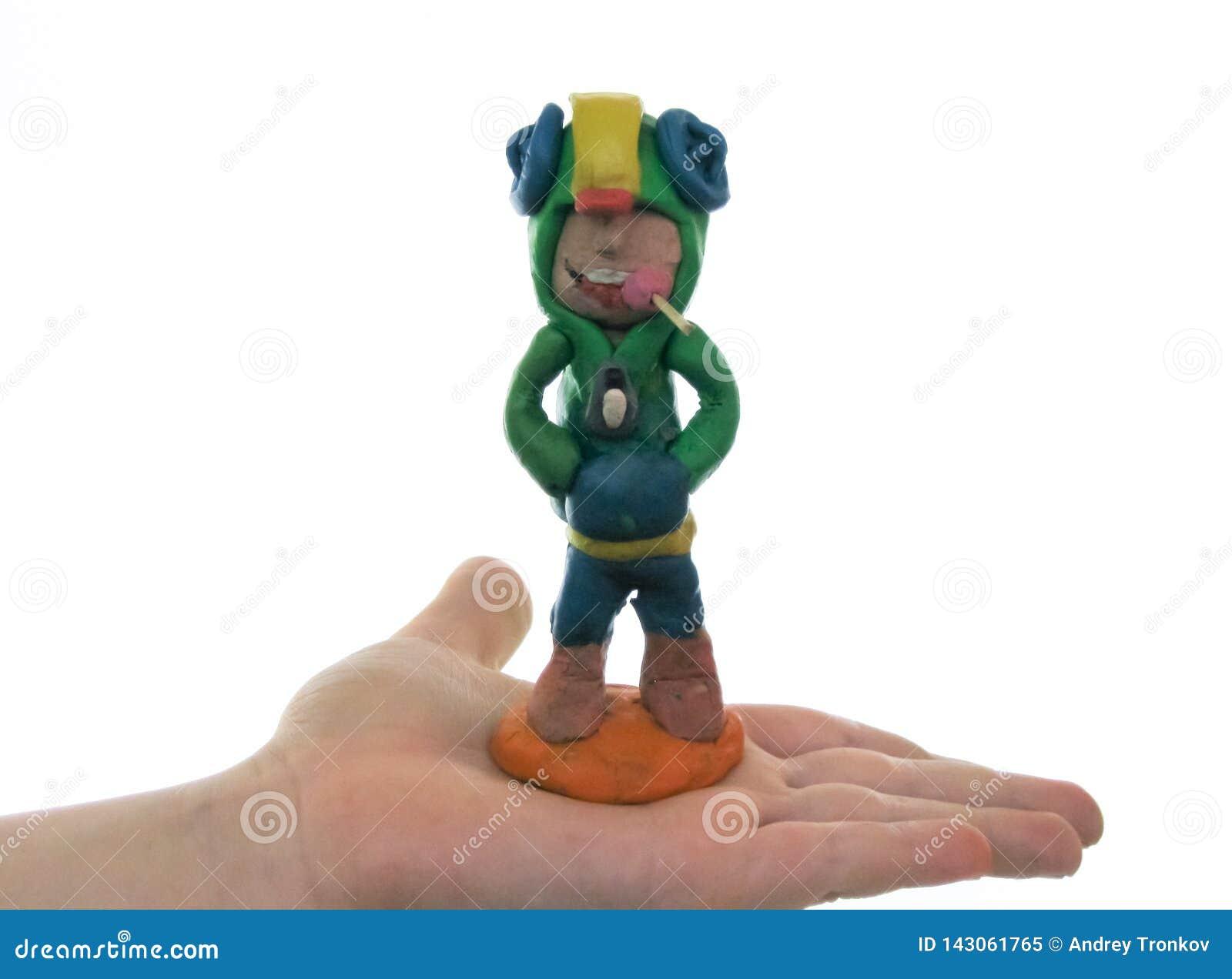 Plastellinapojke med godisen i hans mun, på handen av ett barn