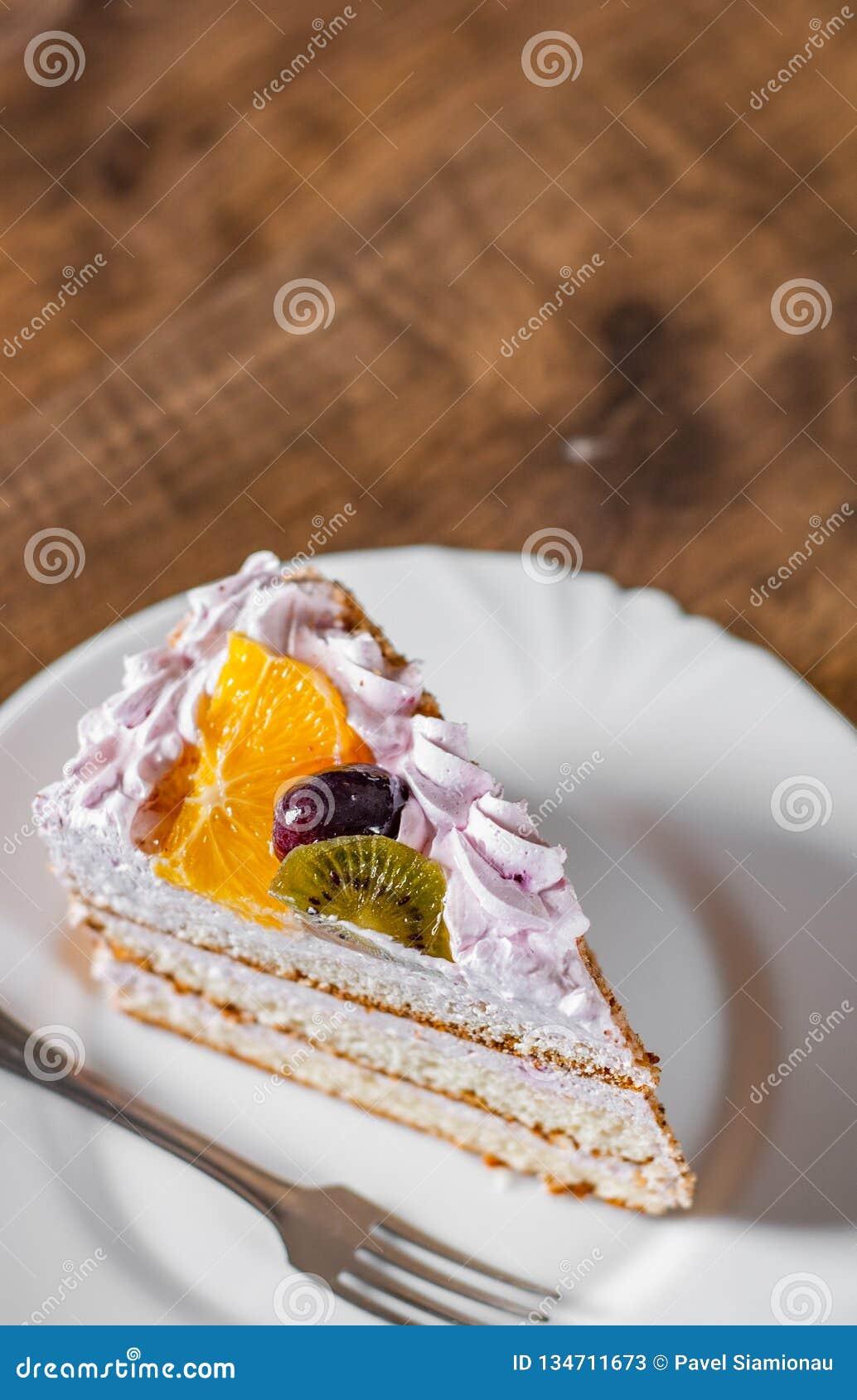 Plasterek płatowaty Urodzinowy tort z śmietanką z owoc w talerzu na drewnianym