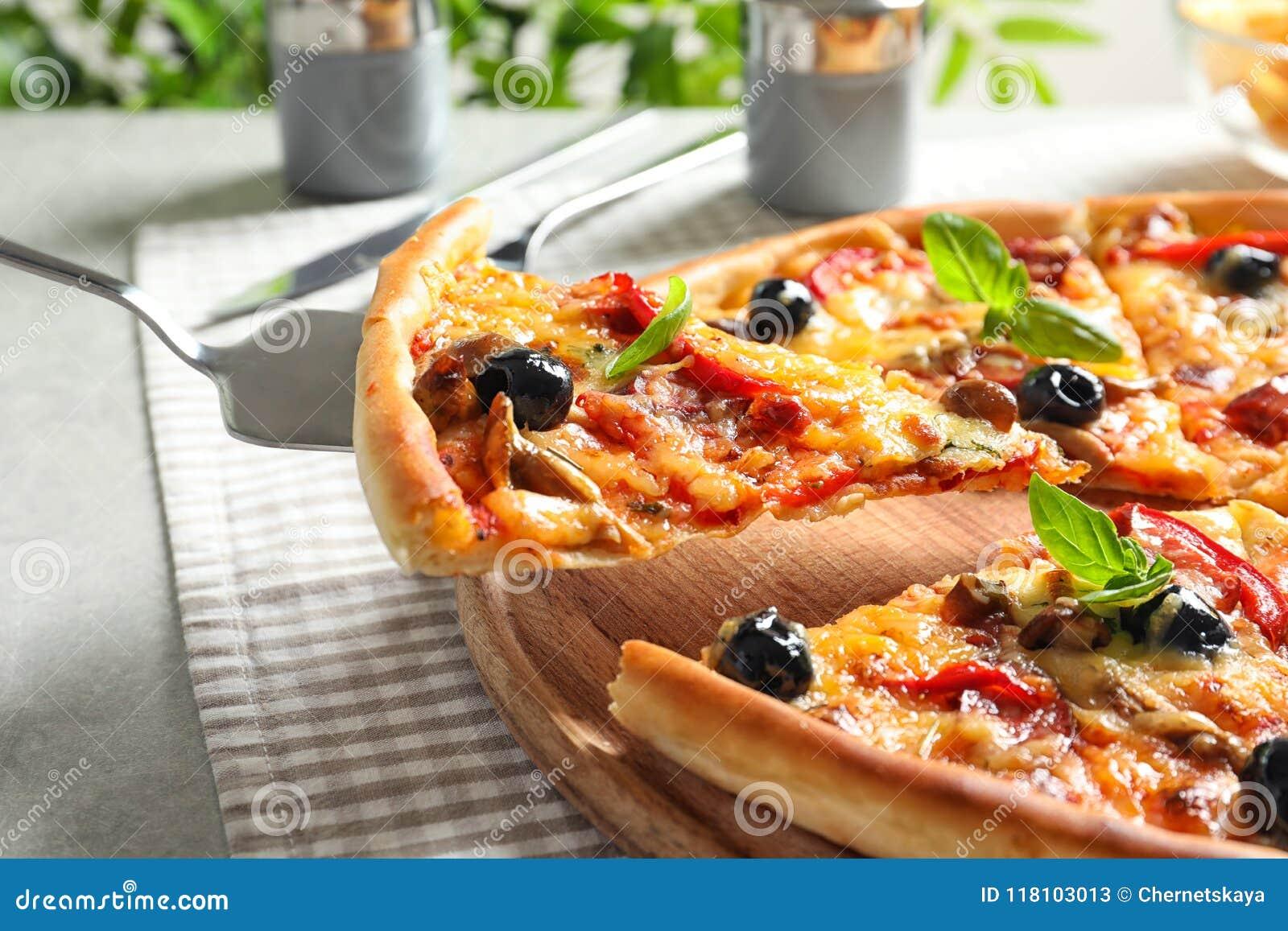 Plasterek smakowita pizza na łopacie, zbliżenie