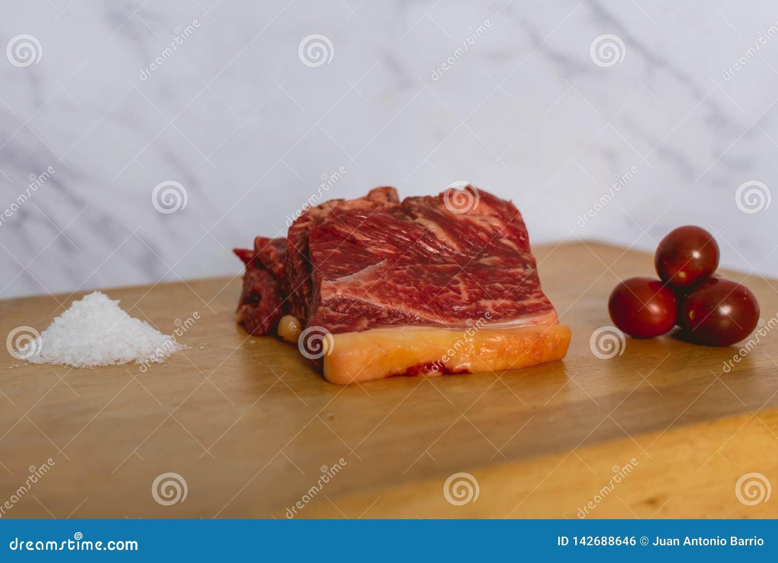 Plasterki świeży surowy wołowina stek na drewnianej desce na białym tle z udziałami prostacka sól i czereśniowych pomidorów ostro