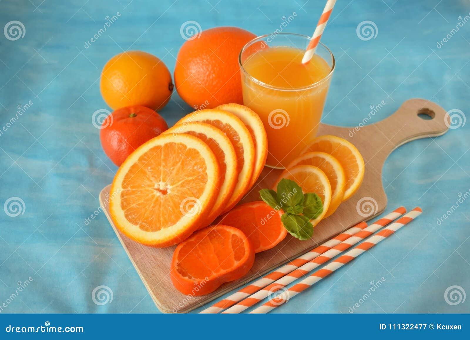 Plasterki pomarańcze, mandarynka, cytryna i koloru żółtego sok w szkle,