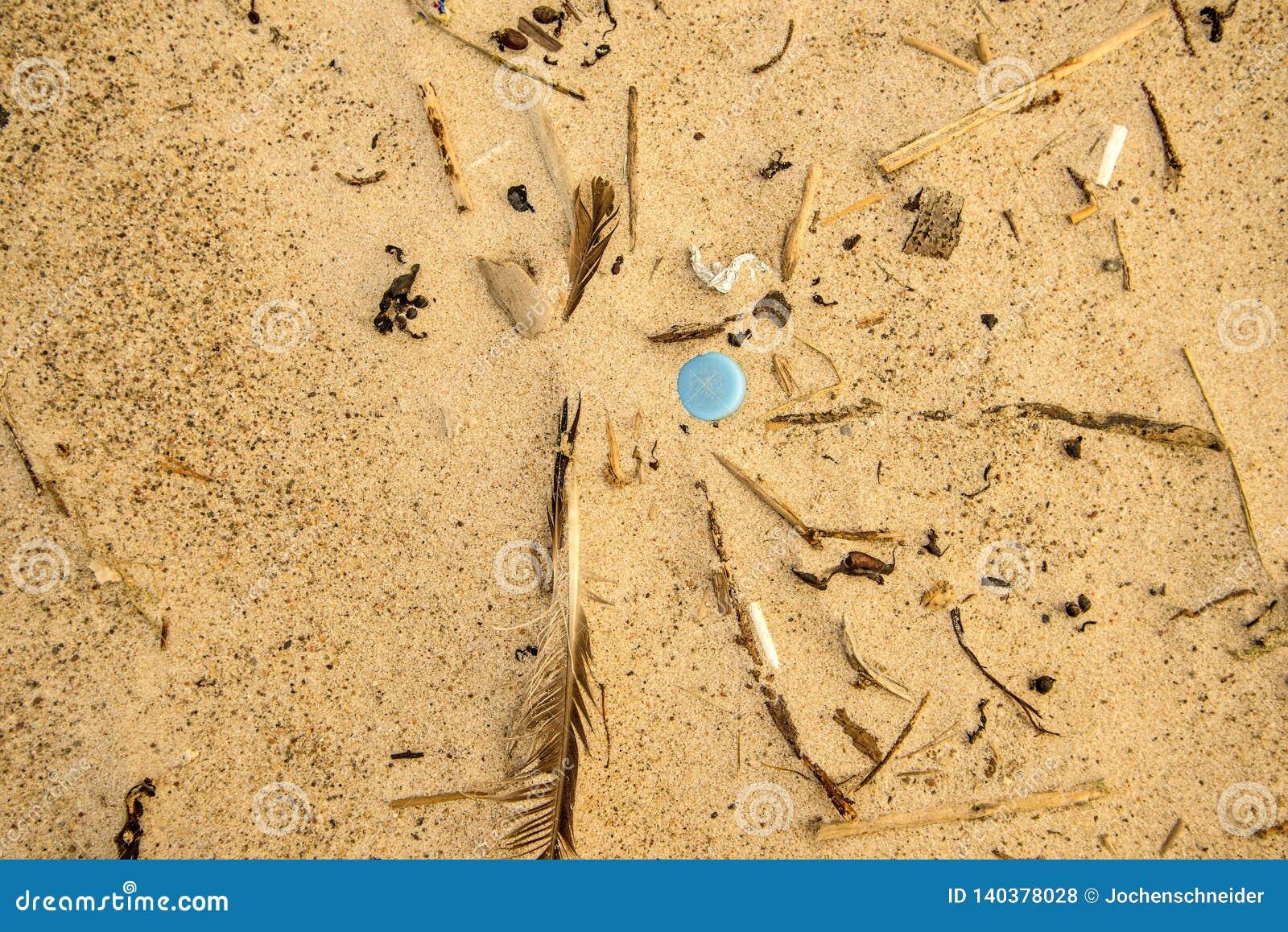 Plastic afval op een strand, blauw deksel