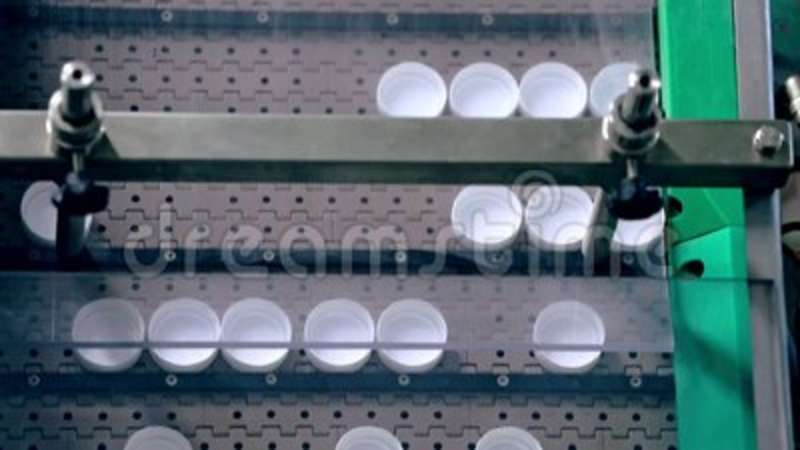 Plastic bottles caps on automated conveyor  Modern equipment for food  packaging