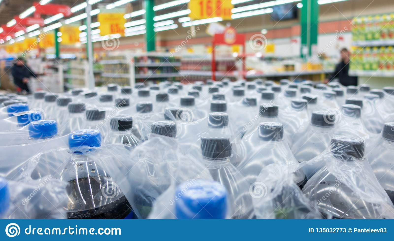 Plastic bottles in packs. Water bottles - plastic bottles factory warehouse store food background.