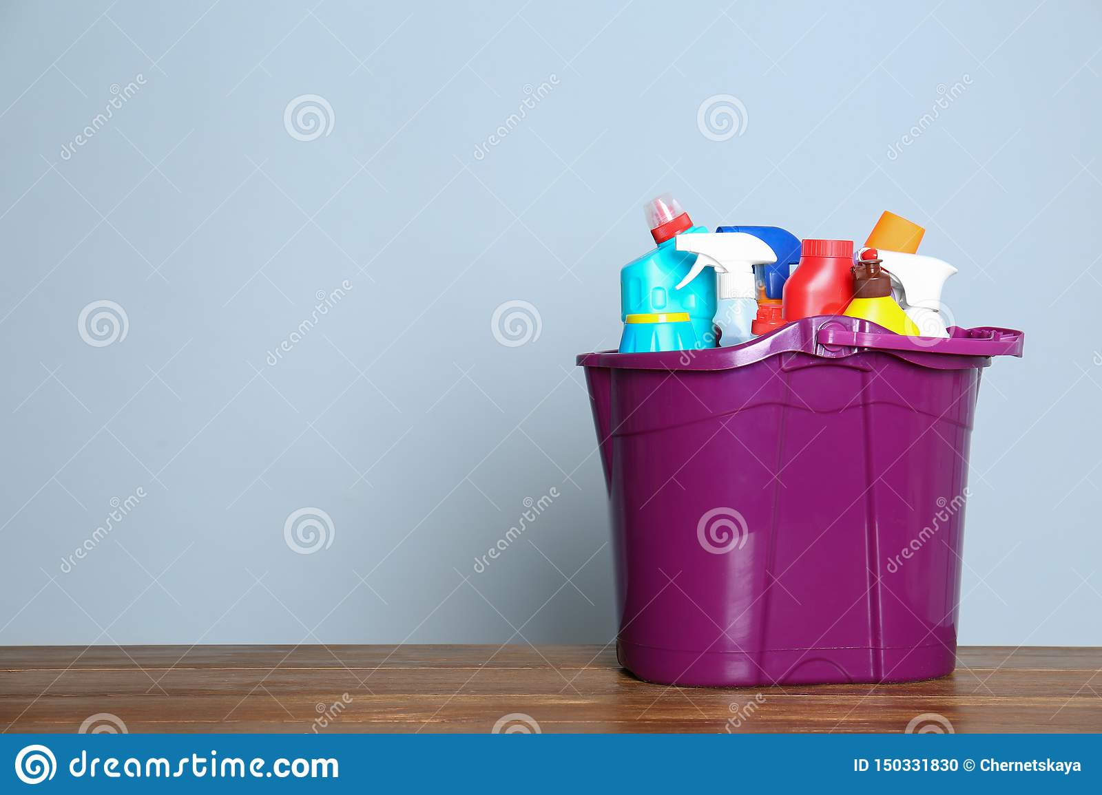 Plastic bucket with different cleaning products on table against color background
