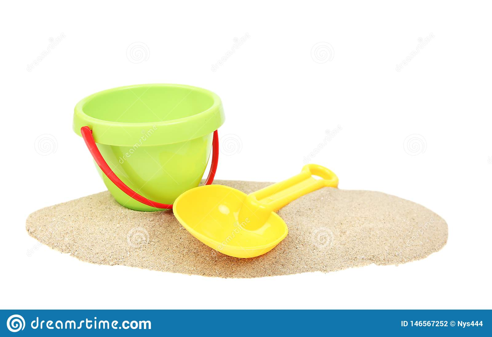 Plastic bucket and showel on sand isolated