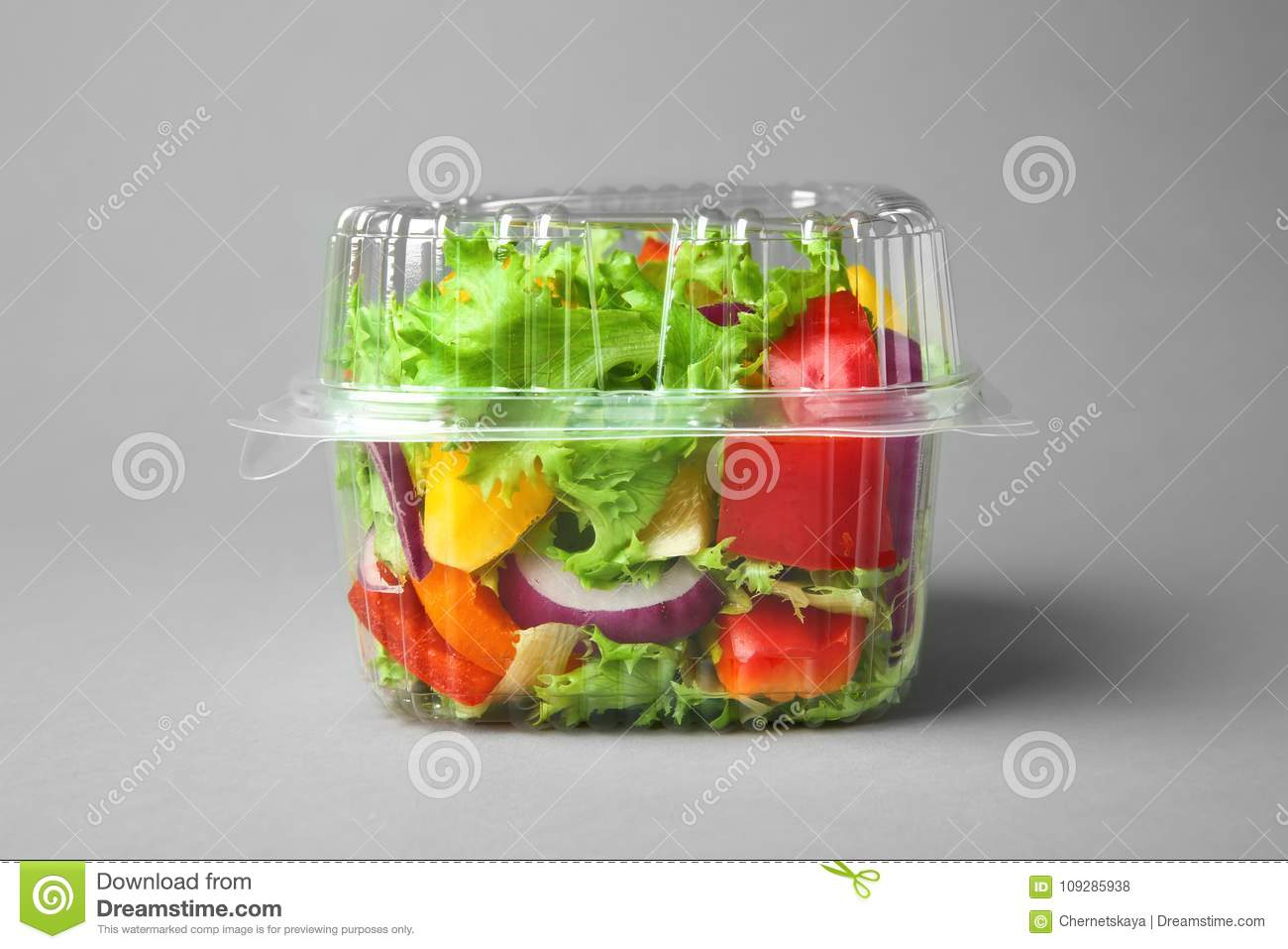 Plastic container with salad
