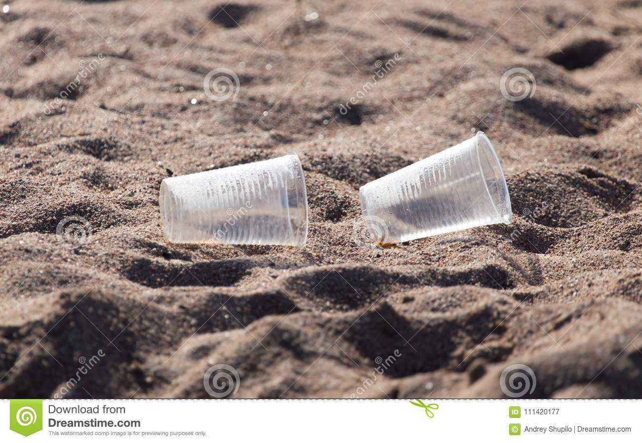 Plastic cup on the sand
