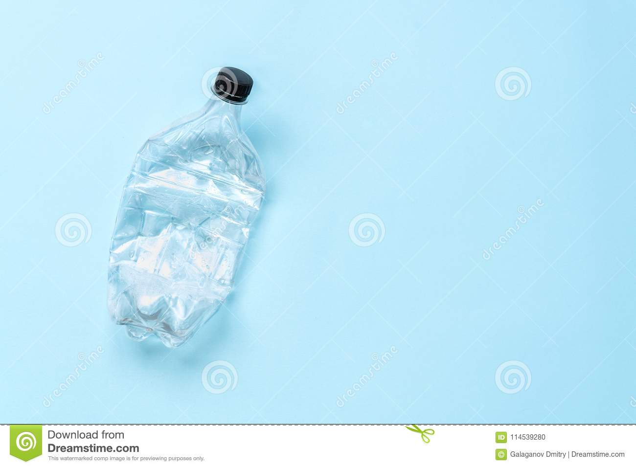Plastic empty rumpled bottle from under the water on a blue background.