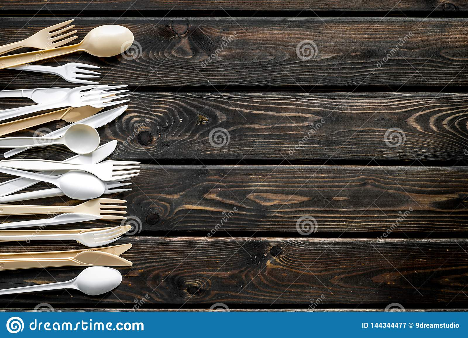 Plastic Flatware For Eco Concept On Wooden Background Top View