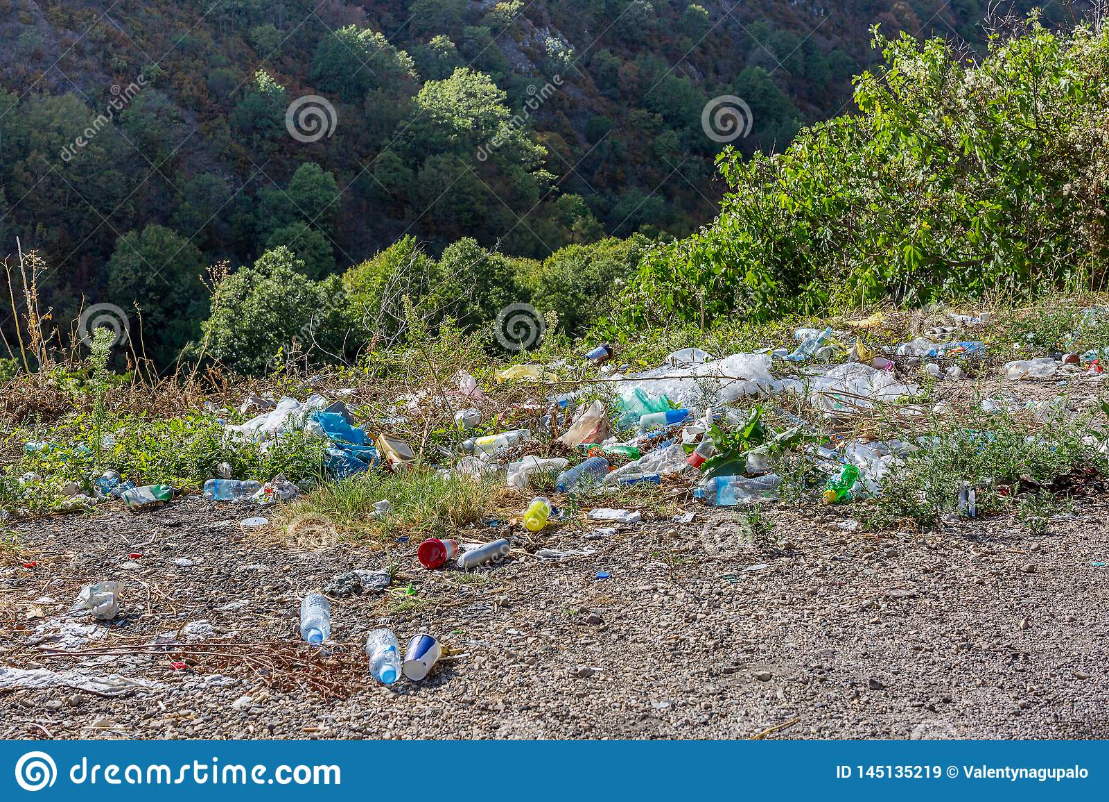 Plastic flessen en ander afval langs de bergweg Heel wat afval bij kant van de weg Concept milieuvervuiling