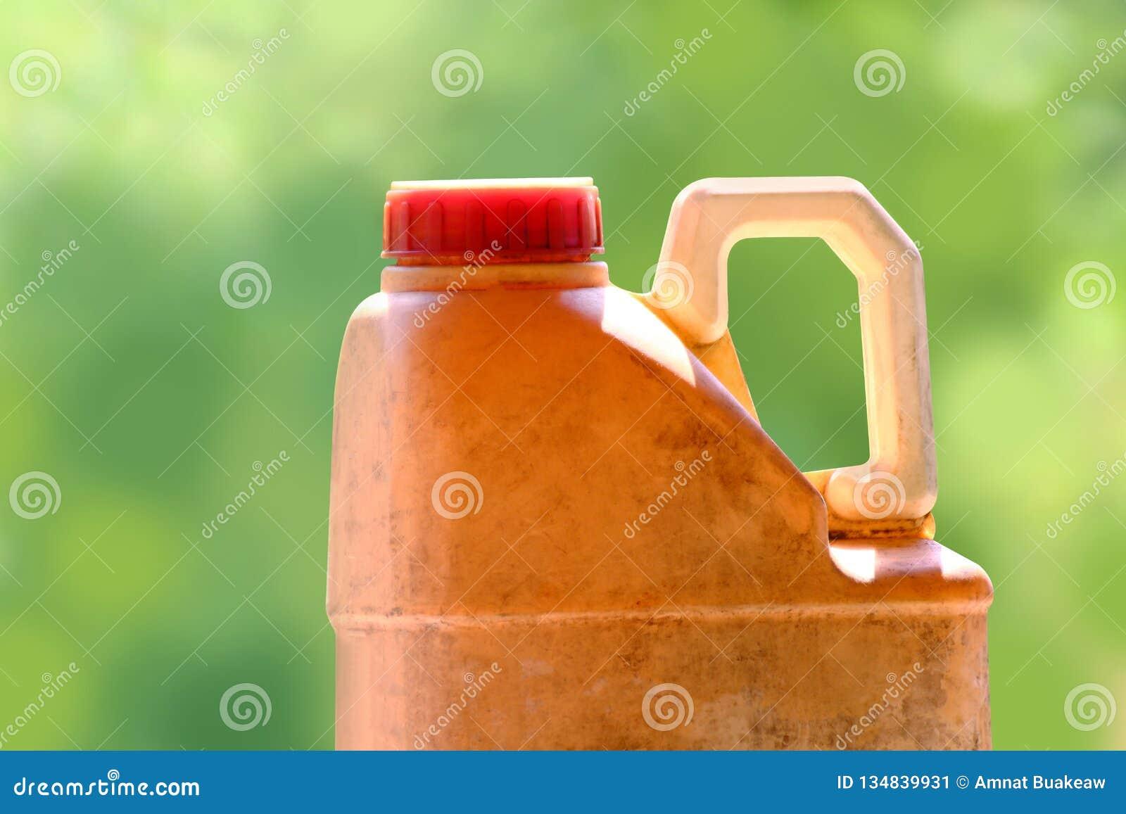 Plastic gallon gele oud van oliesmeermiddel op vage groene achtergrond, sluit omhoog de oude en vuile gallon van de motor van een