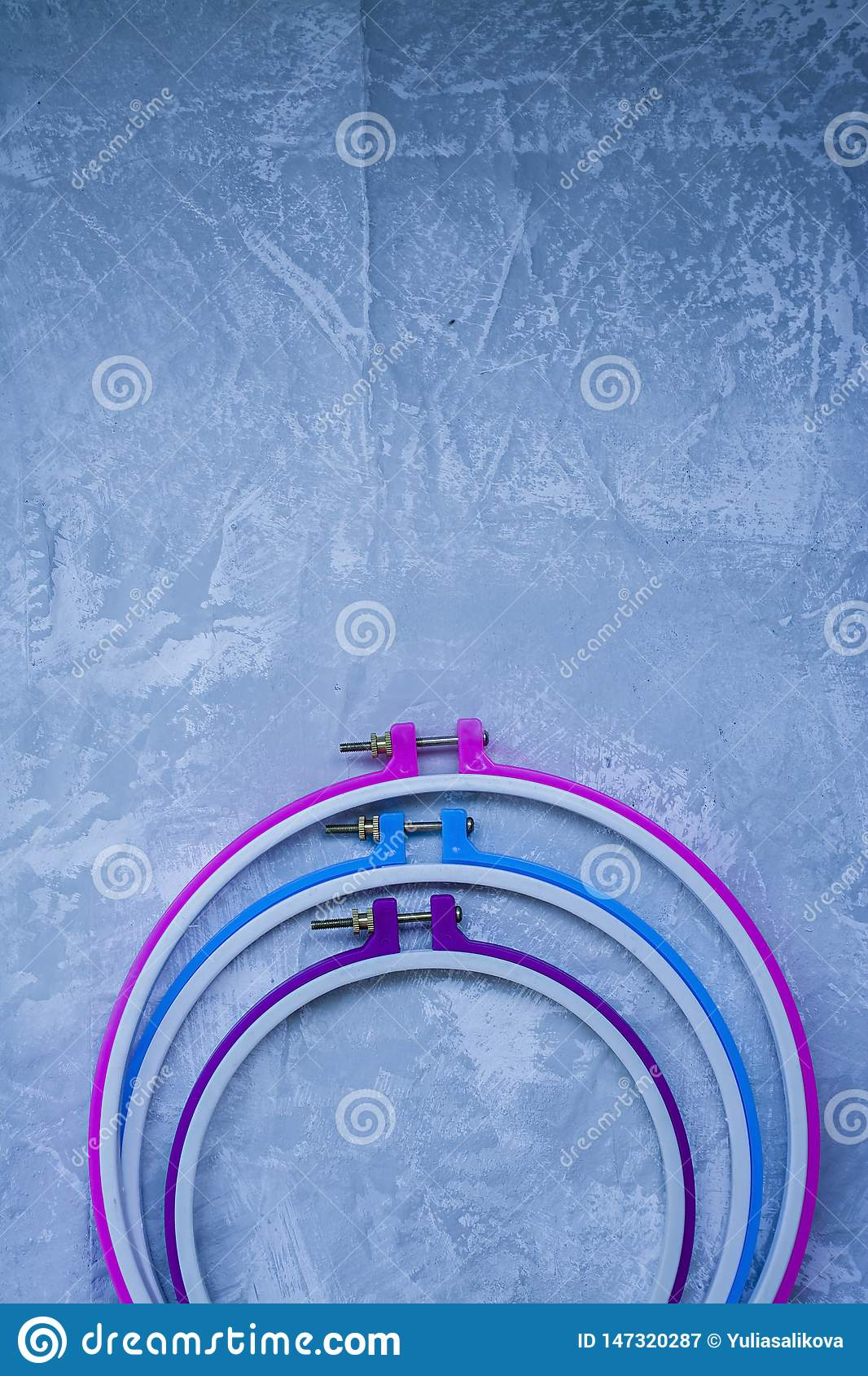 Plastic hoop on a light background under the concrete. Three hoops pink, blue, purple. View from above. Space under the text