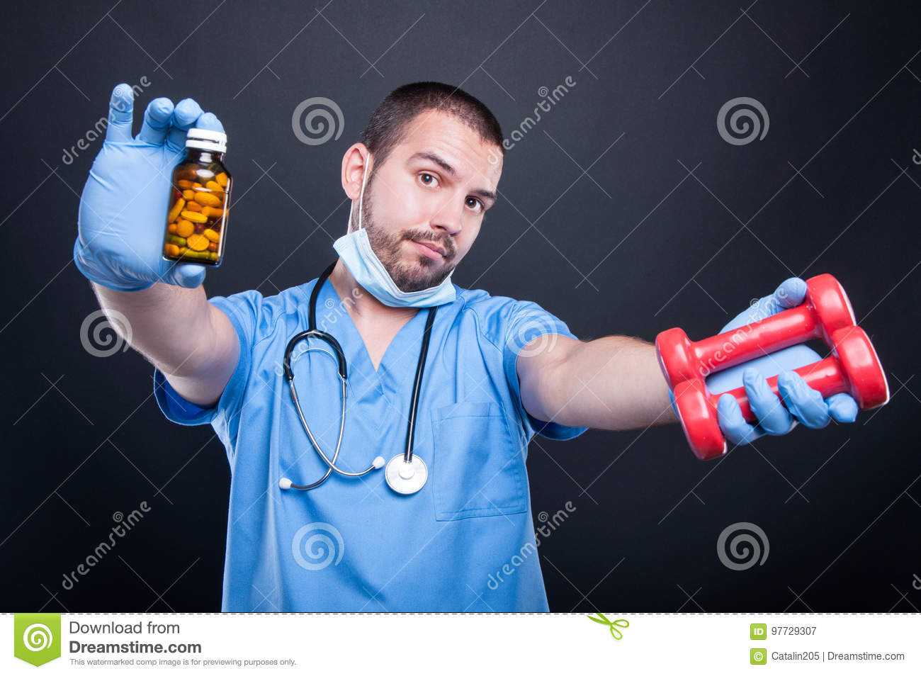 Plastic surgeon wearing scrubs showing dumbbells and pills