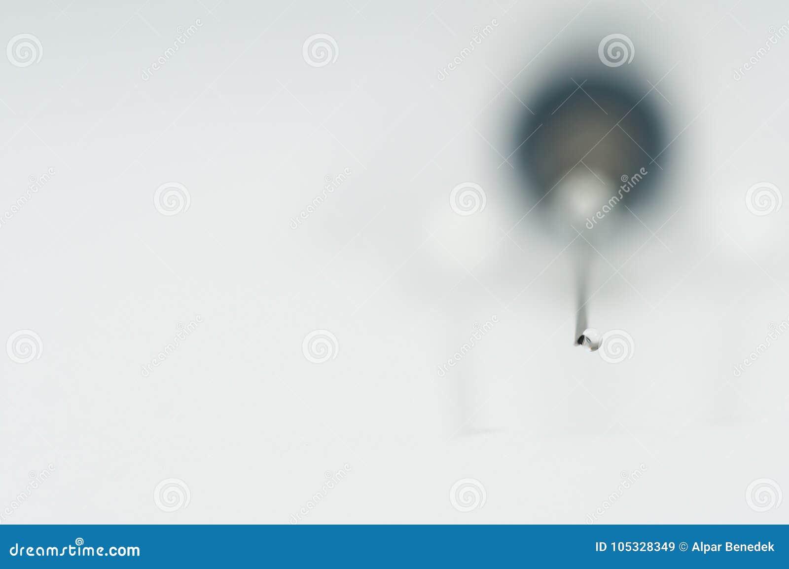 Plastic syringe with needle, focus on the liquid drop.