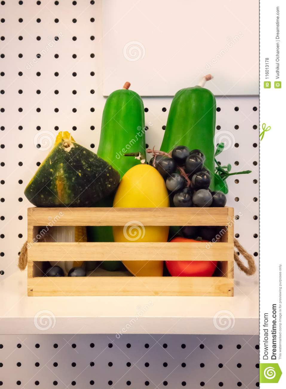 plastic toy fruits and vegetable on wooden basket against