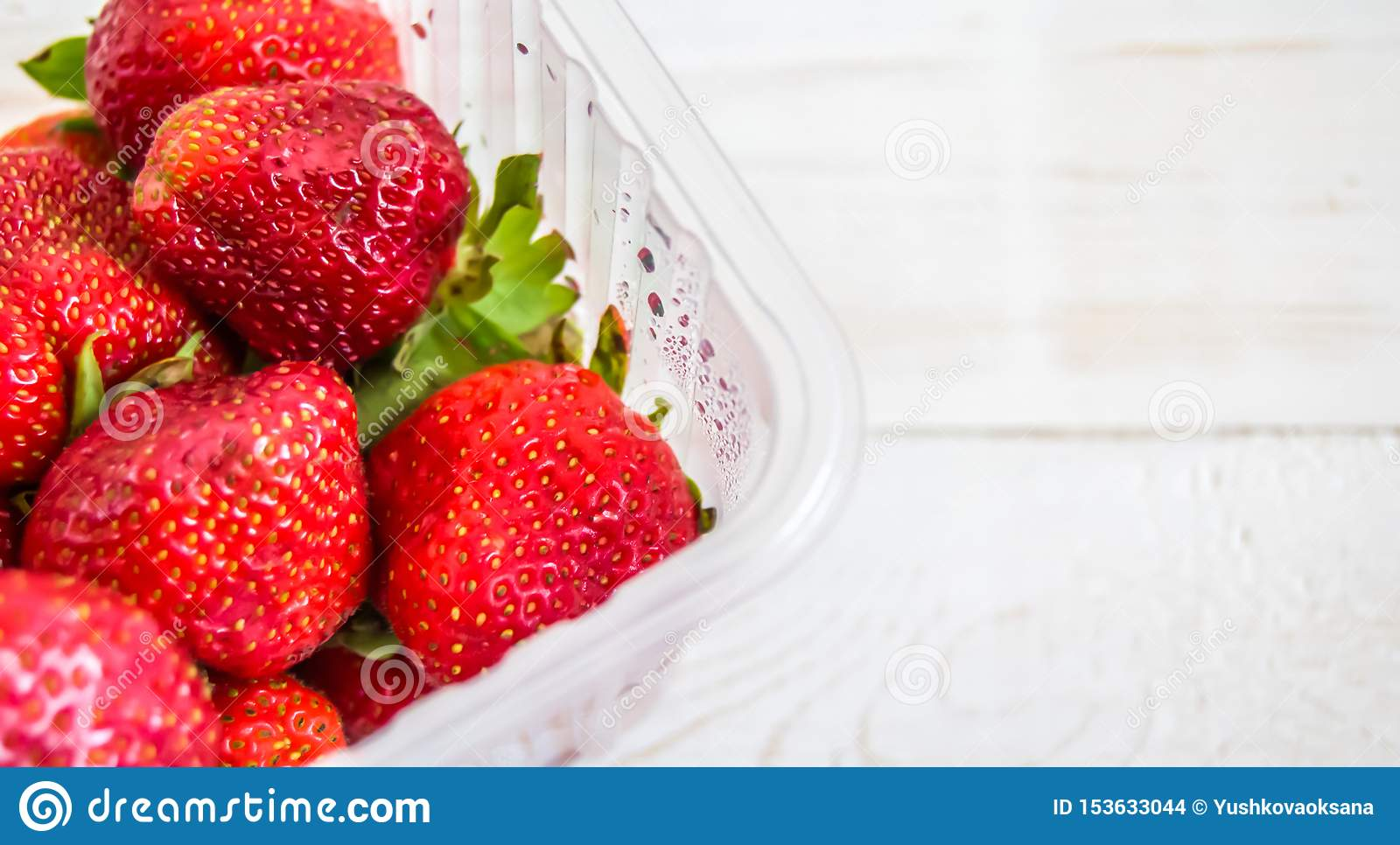 Plastic tray with red strawberries on a white wooden background