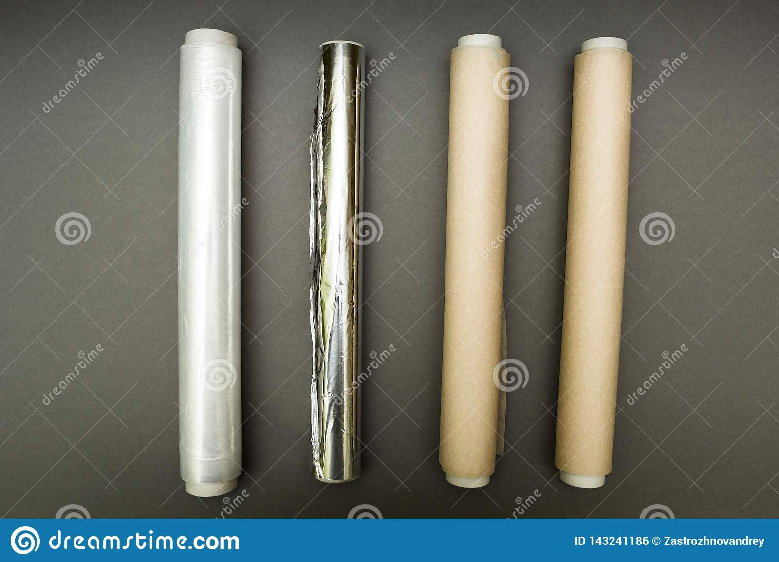Plastic Wrap, Aluminum Foil And Roll Of Parchment Paper On Grey