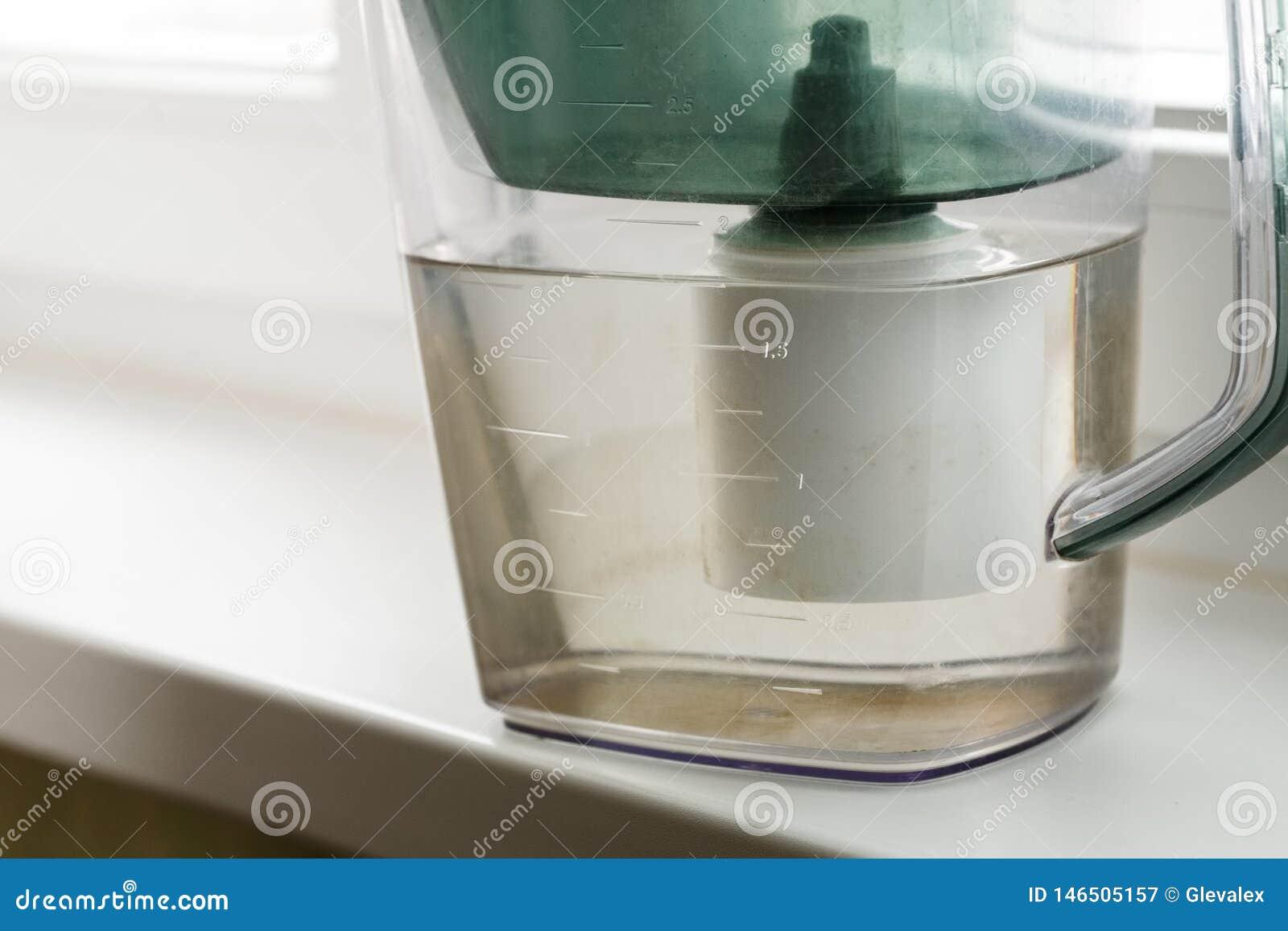 Plastikkrug für Wasserfiltration nah an Fenster