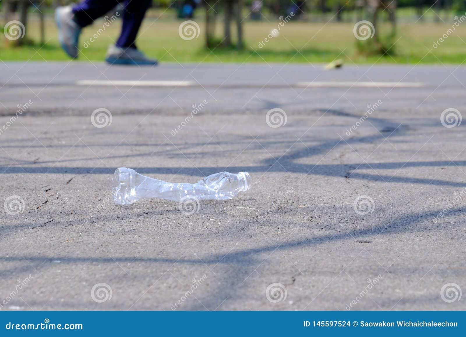 Plastikowa butelka śmieci na drogowym parterze przy zielonym parkiem z mężczyzny bieg na droga przemian woda pitna