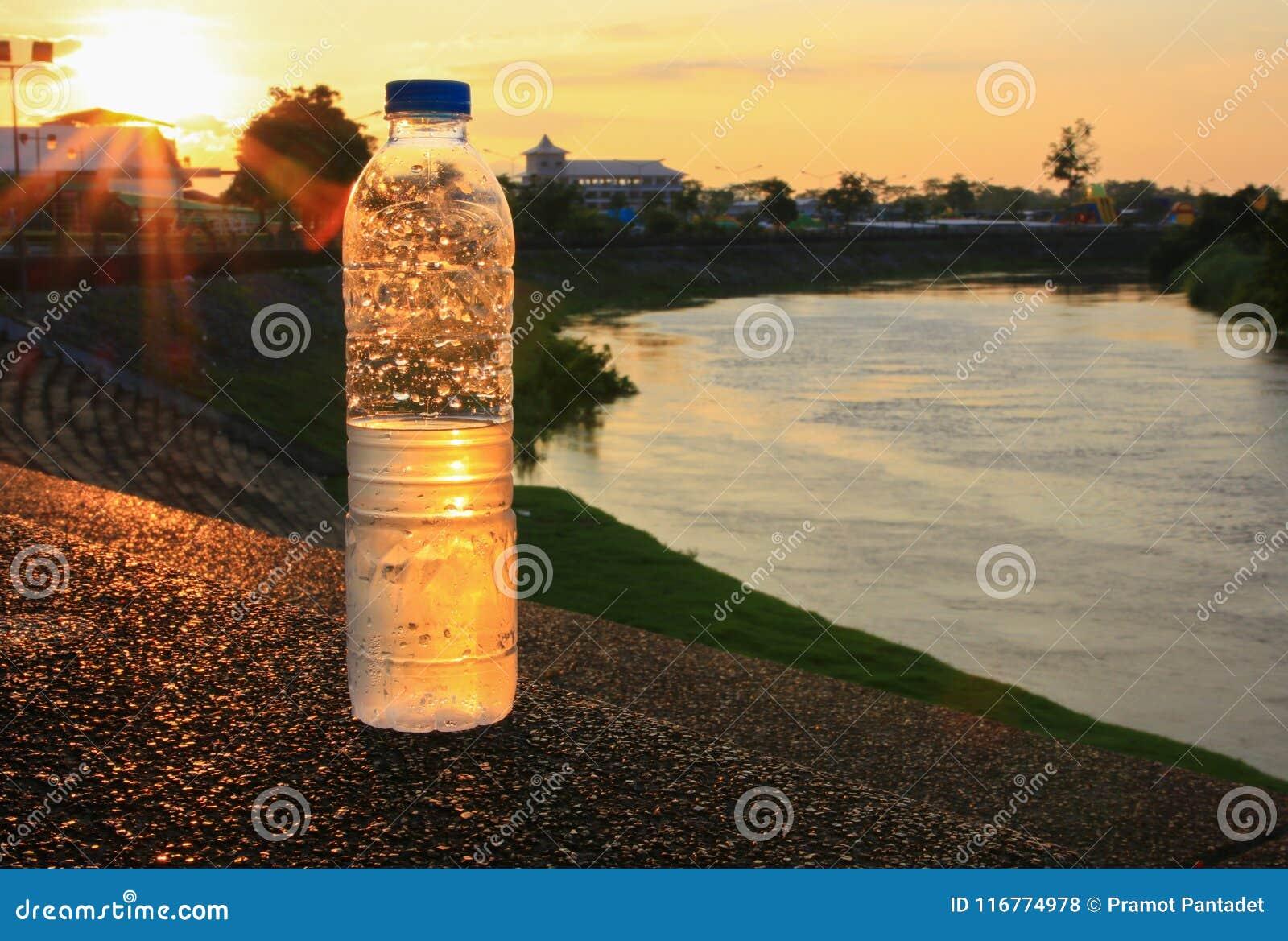 Plastikwasserflasche auf dem Steinboden in einem allgemeinen Park bei Sonnenuntergang, Sonnenaufgangzeit