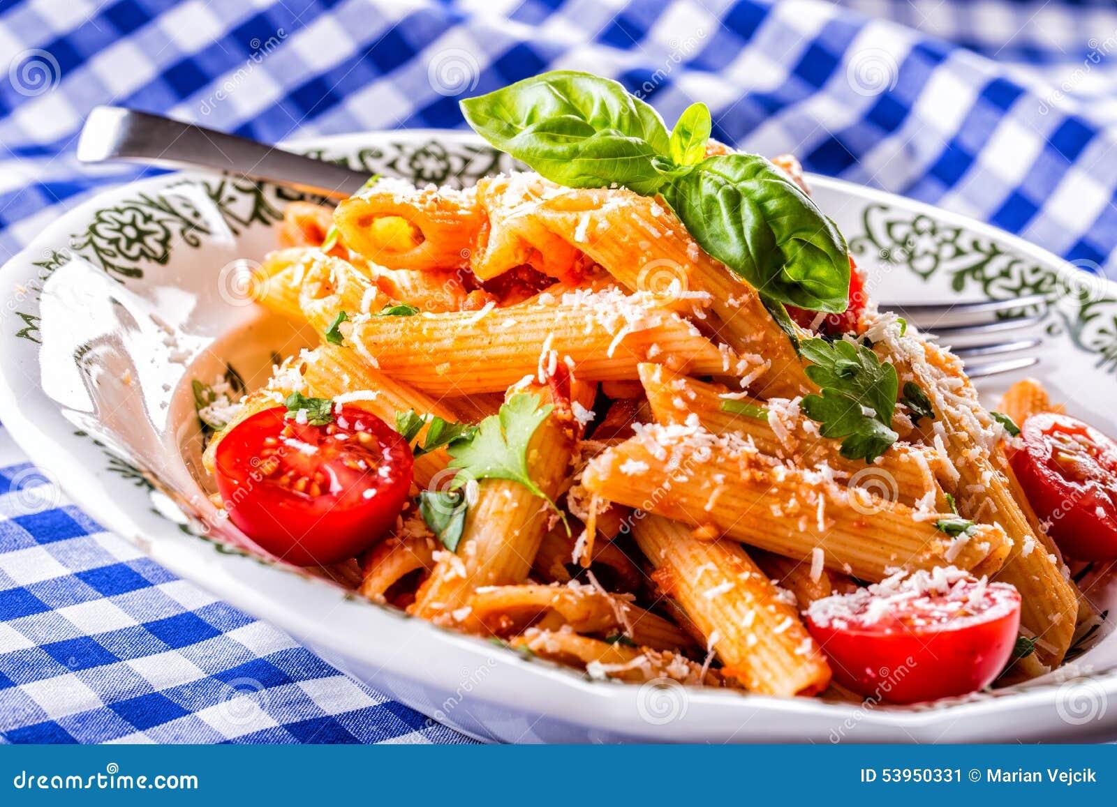 Plat avec les feuilles bolonaises de dessus et de basilic de persil de tomates-cerises de sauce à pene de pâtes sur la nappe bleu