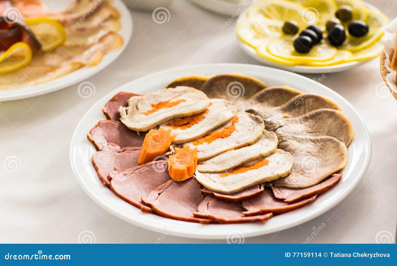 Plat avec les produits carnés découpés en tranches sur la table de fête