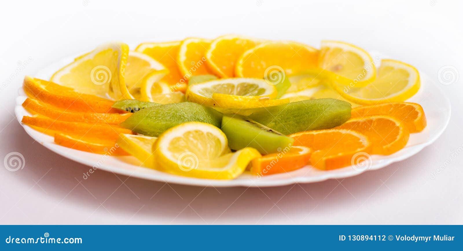 Plat blanc avec des mandarines, des oranges et le kiwi sur une table de fête
