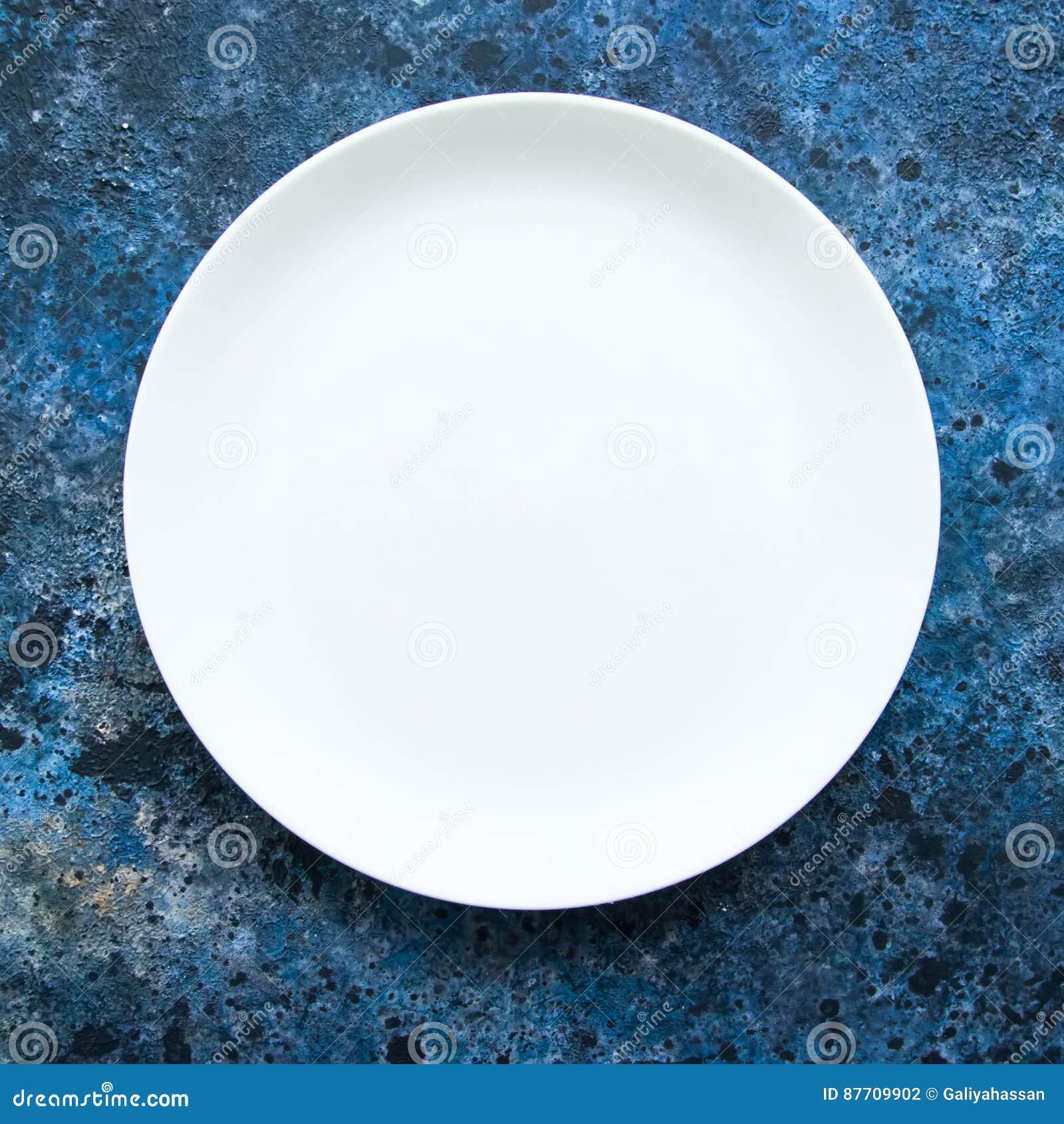 Plat blanc vide rond sur un fond texturisé bleu Vue supérieure