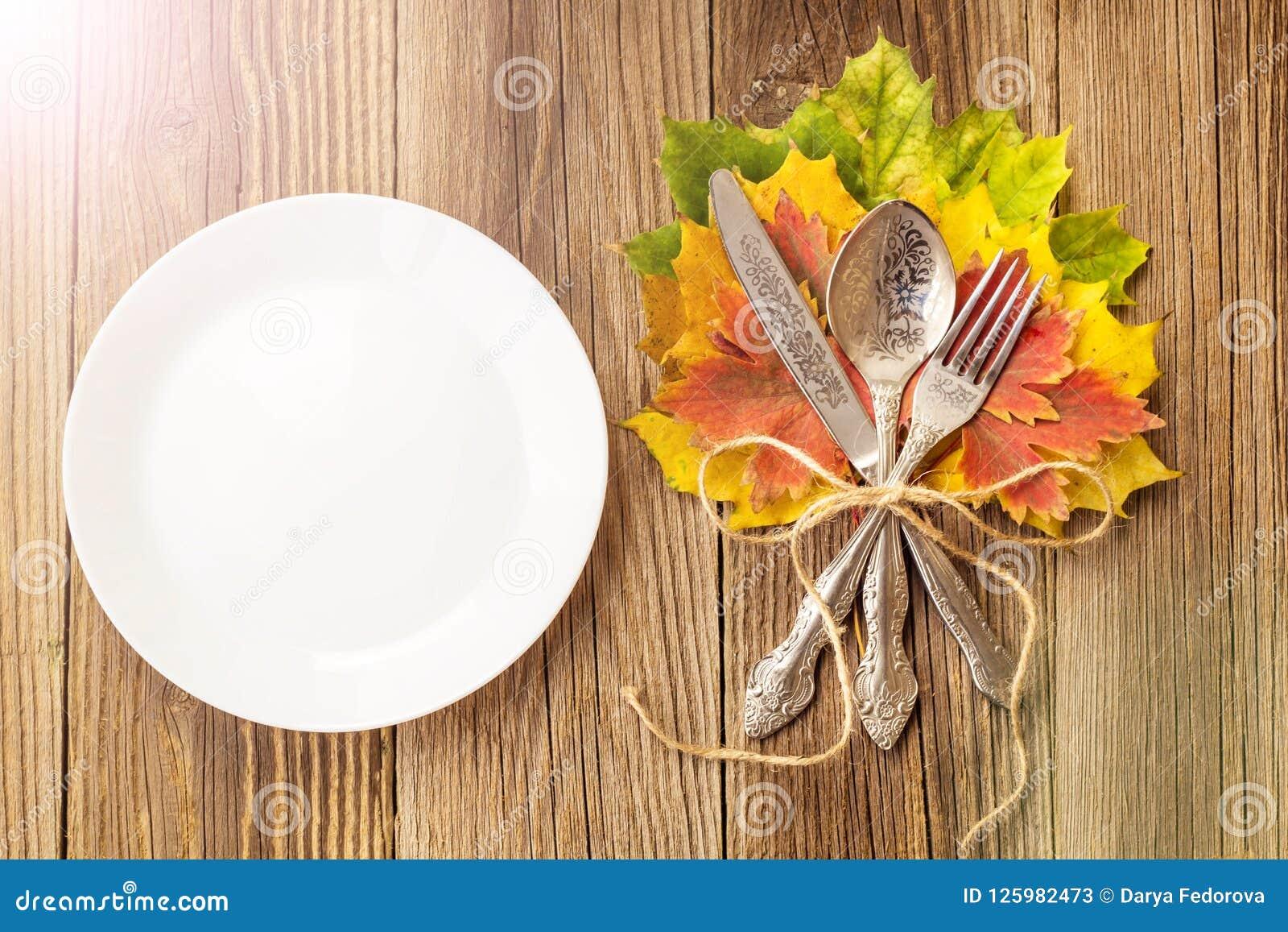 Plat de dîner de thanksgiving avec la fourchette, le couteau et les feuilles d automne sur le fond en bois rustique de table Vue