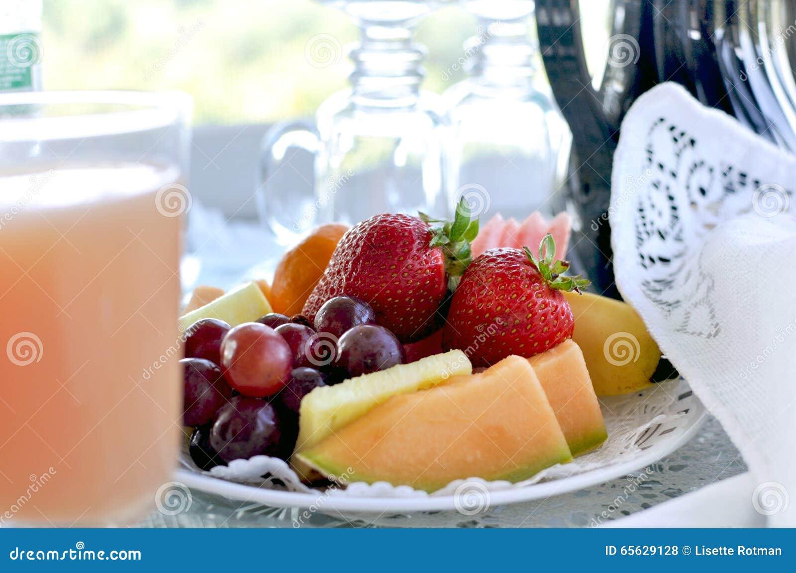 Plat de fruit avec du jus au lit - et - petit déjeuner