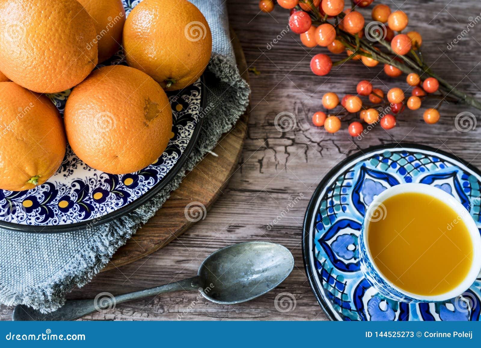 Plat fait main espagnol bleu avec les oranges, le jus et la cuillère d argent sur la table en bois