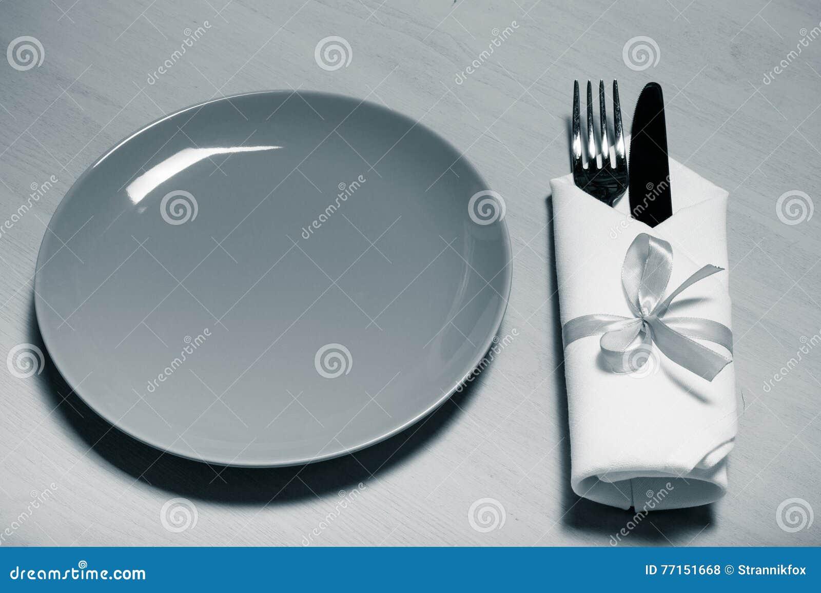 Plat, fourchette et couteau dans la serviette sur le fond en bois toned