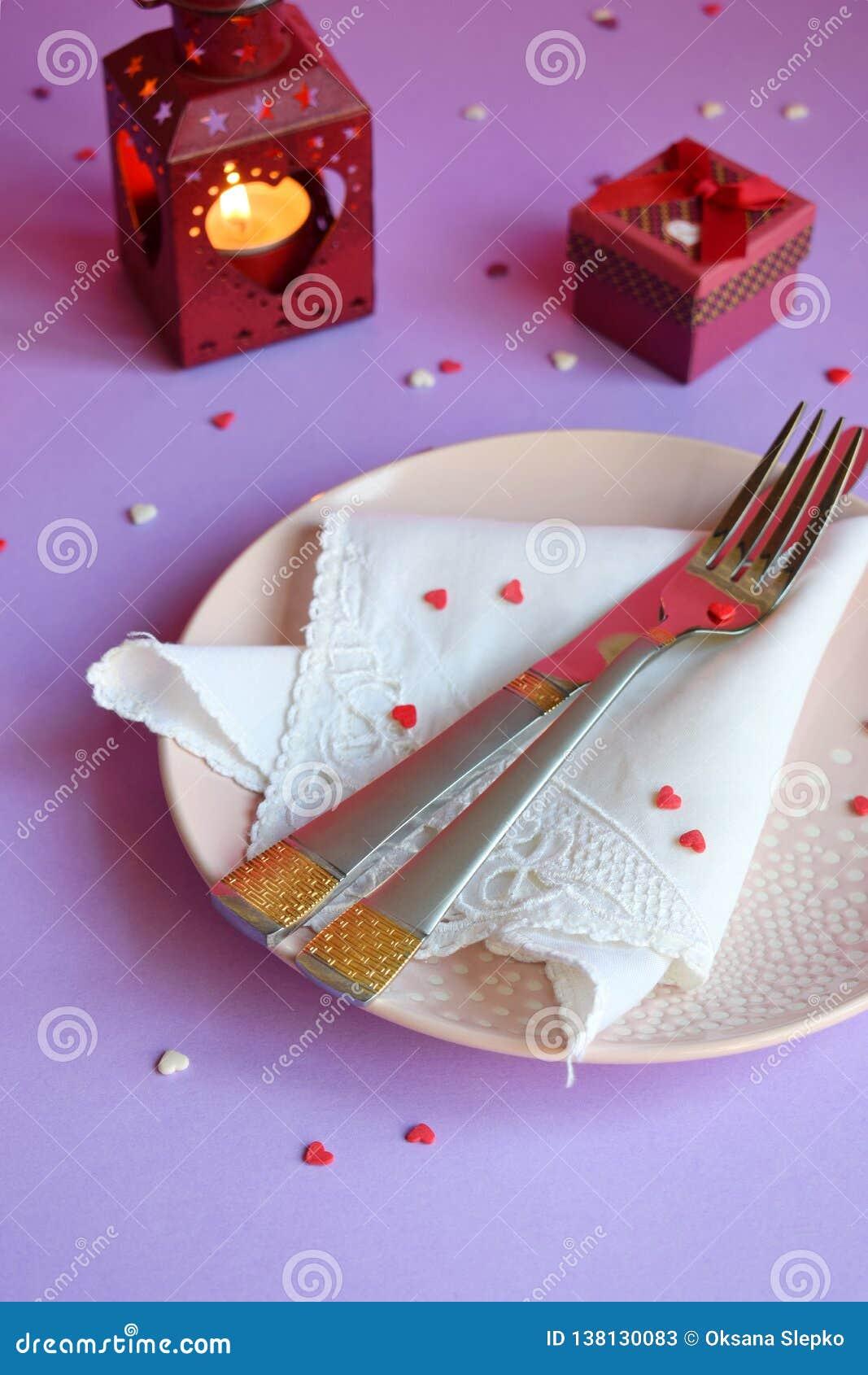 Plat rose vide, couverts, coeurs, chandeliers et cadeau rouge sur le fond rose-pourpre Concept d arrangement de table de Saint-Va