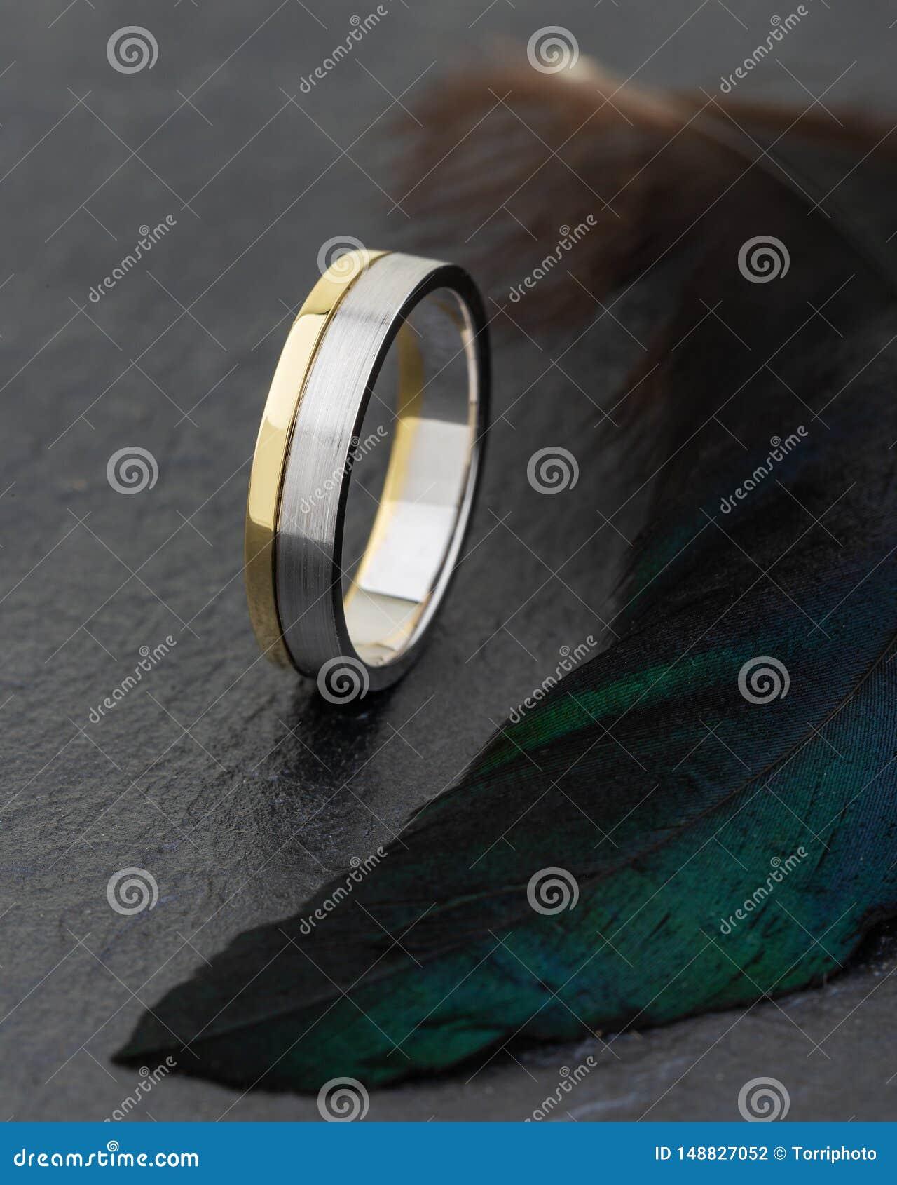 Plata y anillo combinado oro en fondo negro con el feathe verde