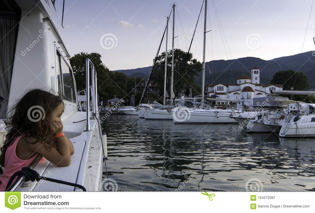 PLATAMONAS, GREECE - August 25 2018: Little girl looks at the sea and the boats on harbour on Platamonas, Greece