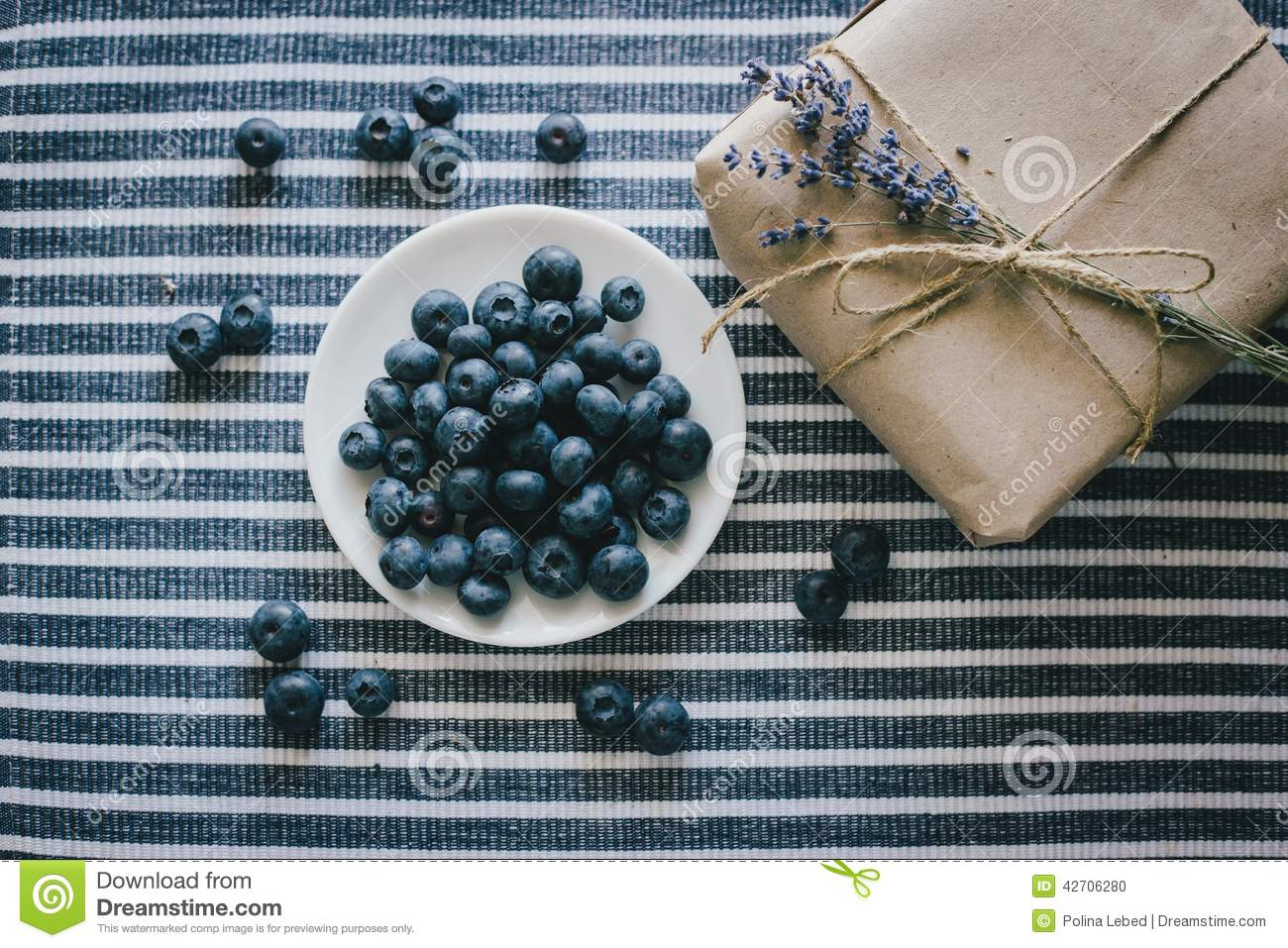 e8ce9b9ee07 Plate with blueberries on a striped tablecloth standing near wrapped  present with lavender