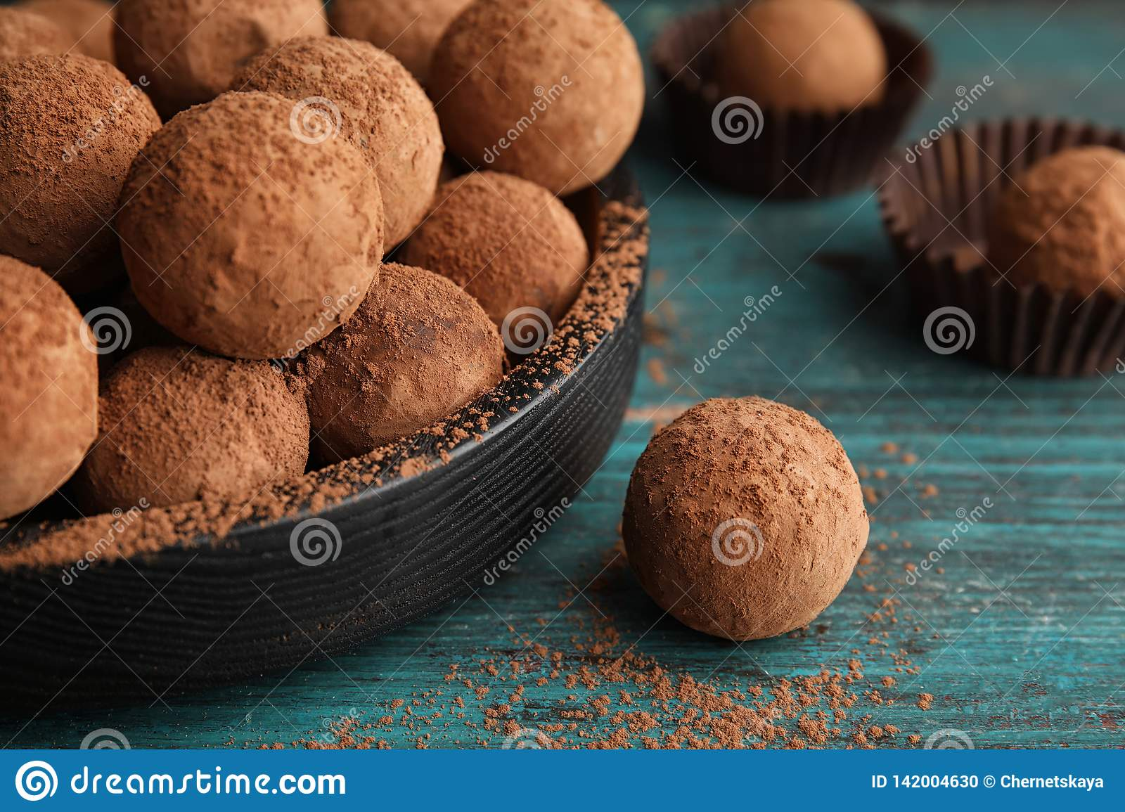 Plate of chocolate truffles on wooden background
