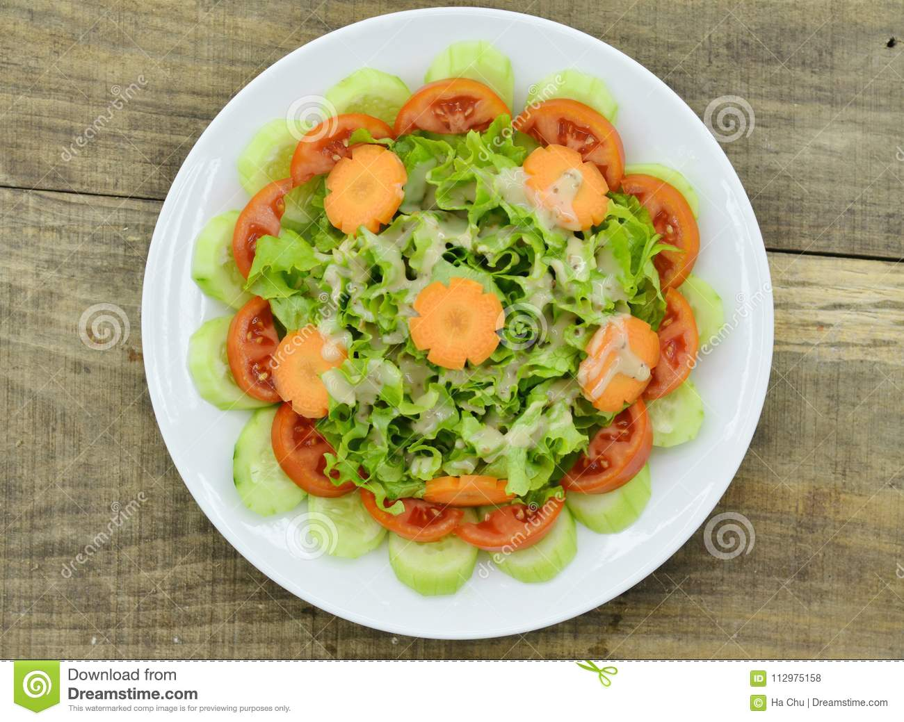 Plate with delicious carrot salad on wooden background